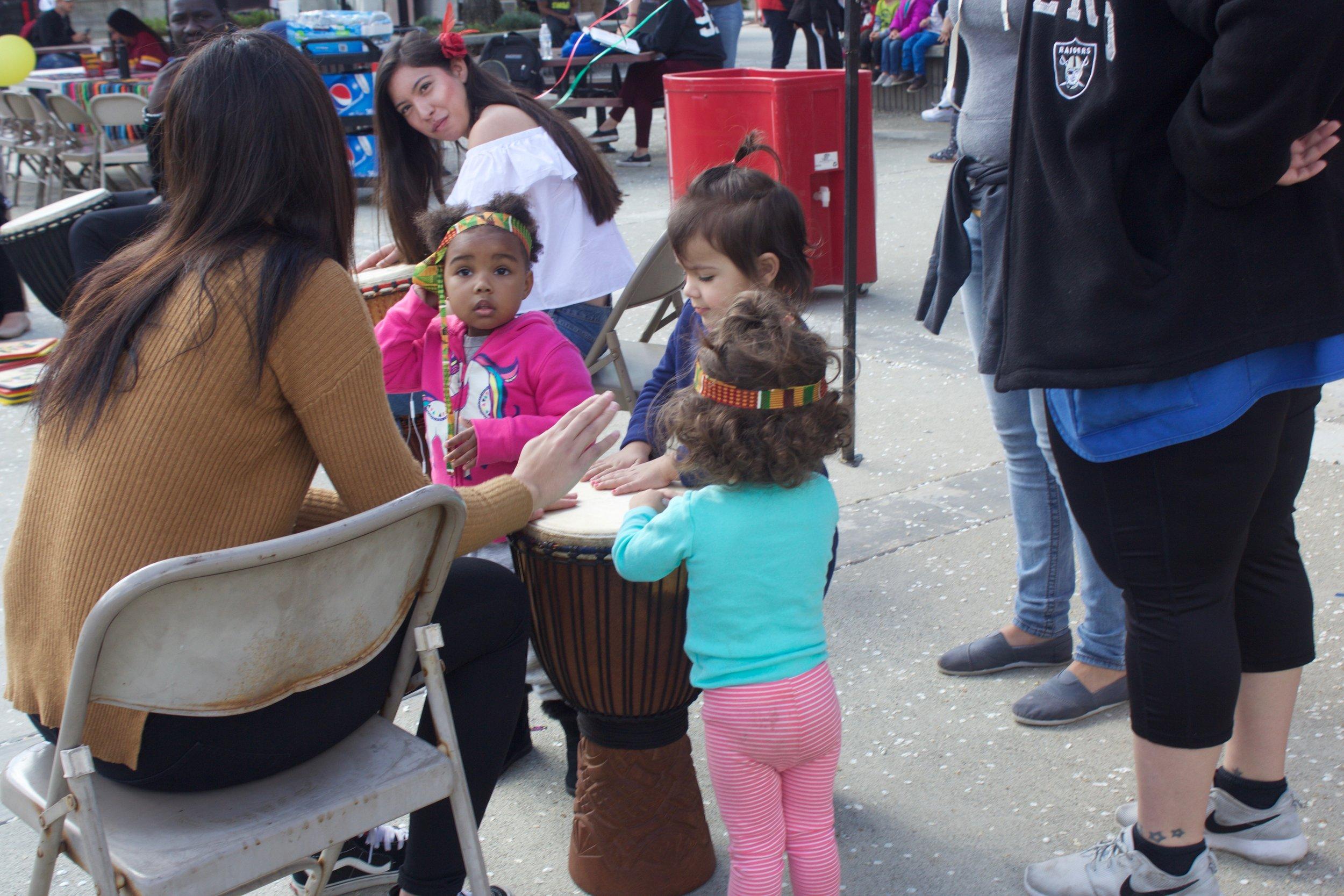 Children bang on a drum during the African Village Event on Feb. 22. Photo by Esmerelda De Santiago