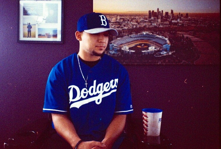 Jacob Salazar in front of his picture of the Dodger Stadium and Los Angeles skyline.