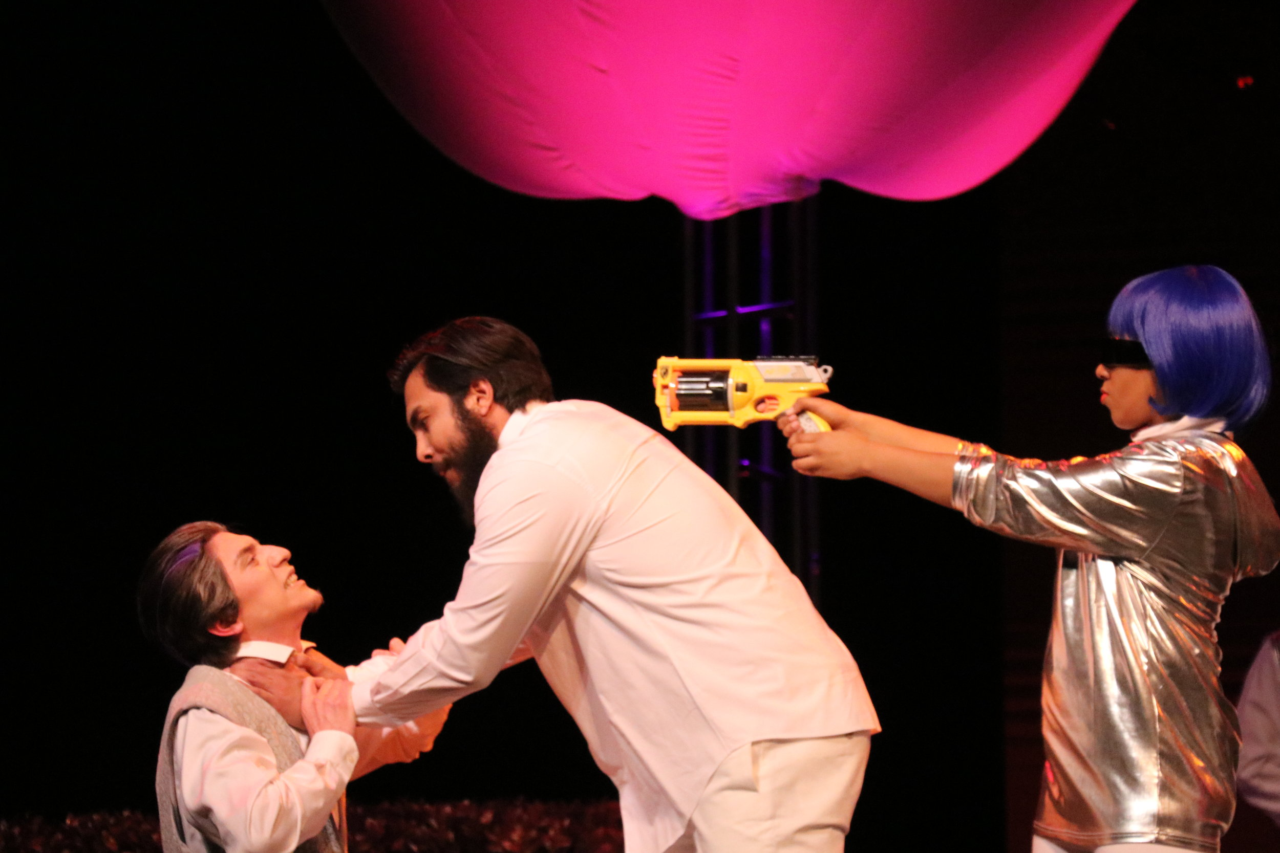 "A scene from ""As You Like It."" A gun is pointed at the lead, Orlando, as he fights with his brother. Photo by Ciara De Alba."
