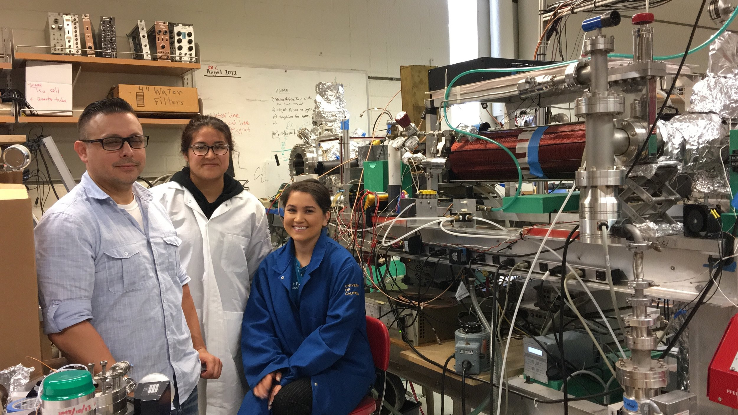 Miriam Contreras, Audrey Vasquez and Marcus Asaro pose in front of the steel machinery in the laboratory at University California, Riverside. Photo by Kiara Jerez.