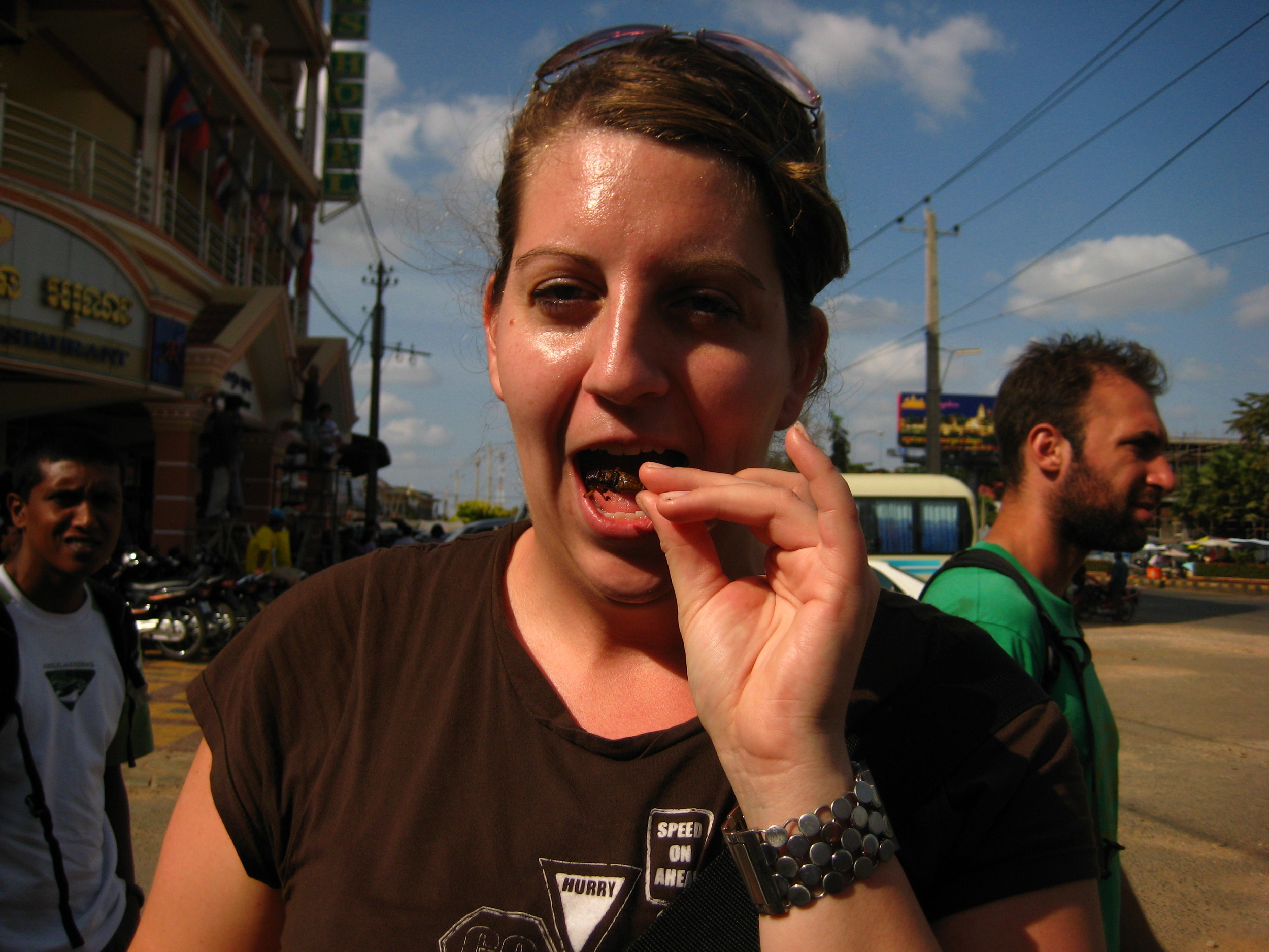 Eating a cricket in Cambodia.