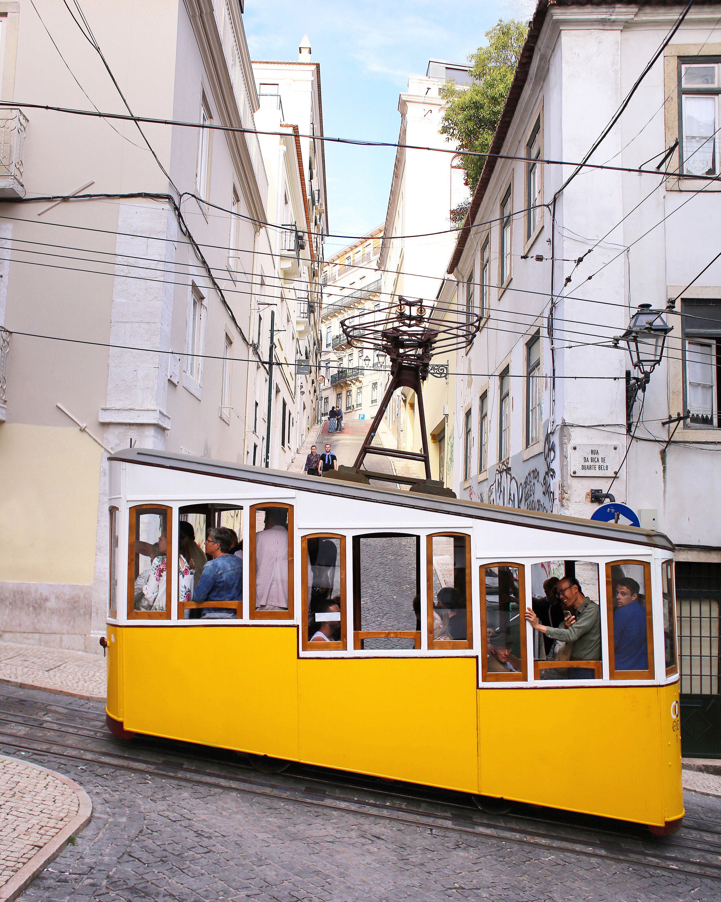 The   Ascensor Da Bica  is a funicular consisting of two adorable yellow tram cars that run up and down the hilly streets of Lisbon since 1892, transporting locals but mostly tourists these days.