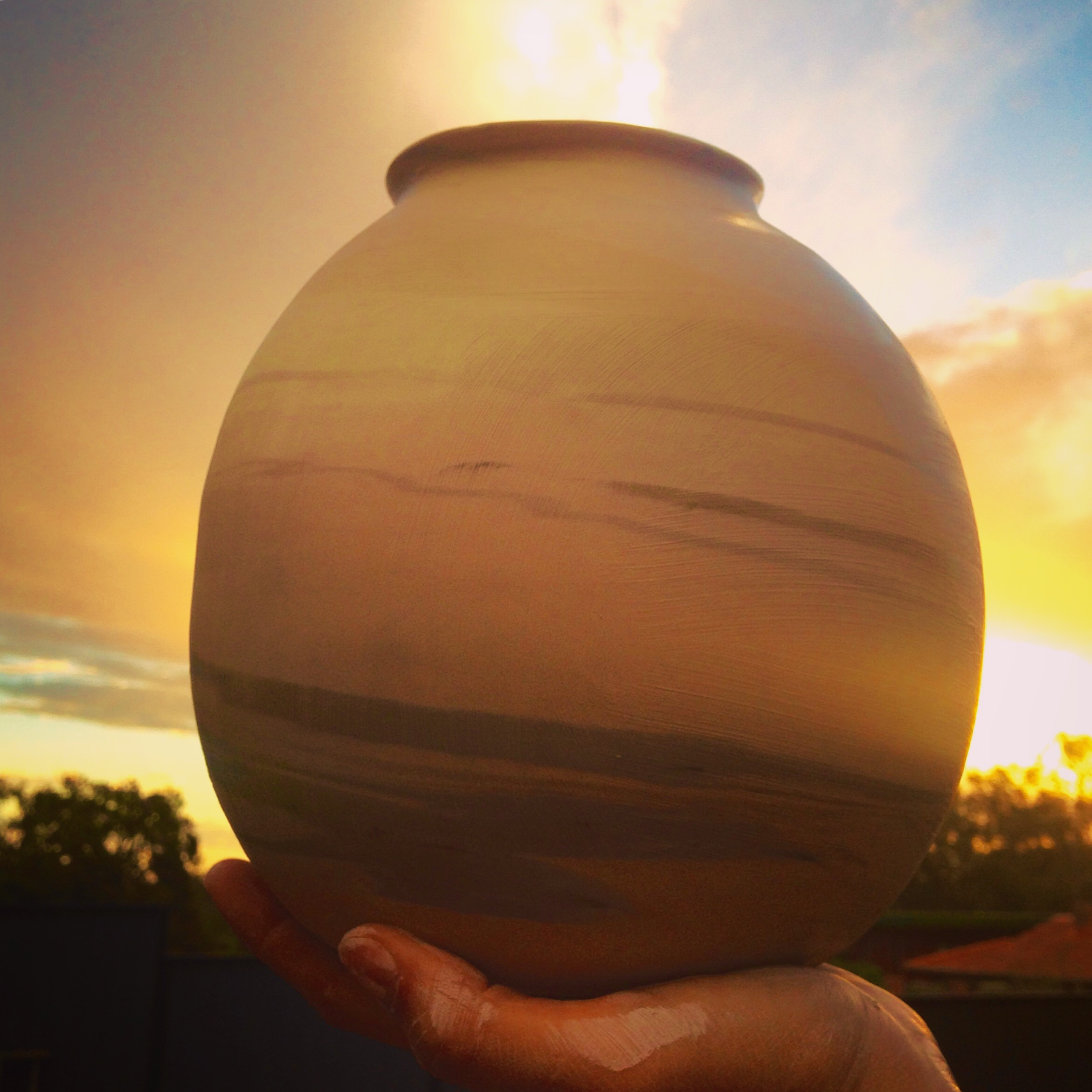 A moment in time captured- as it turns to dusk and the sun starts to set, the heavy storm clouds give way to the light. Photo taken at my studio as I have just finished throwing this vessel on the wheel.