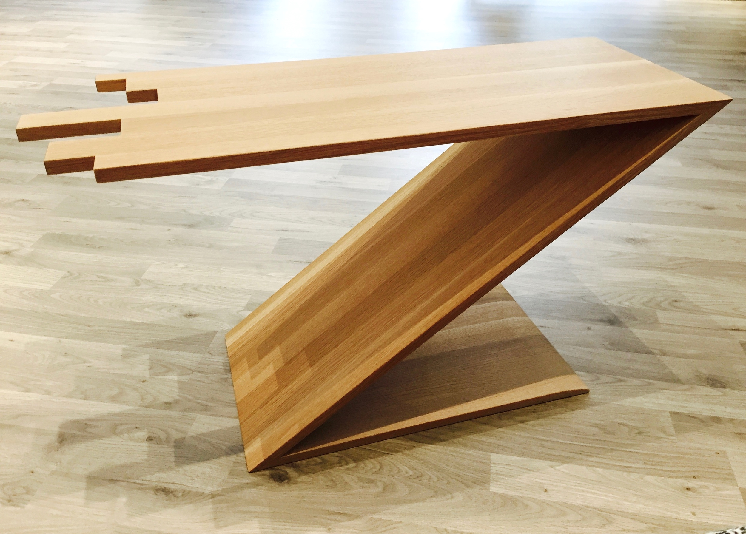 A longer table top with the shorter gently sloping base creates an illusion of uncertainty.