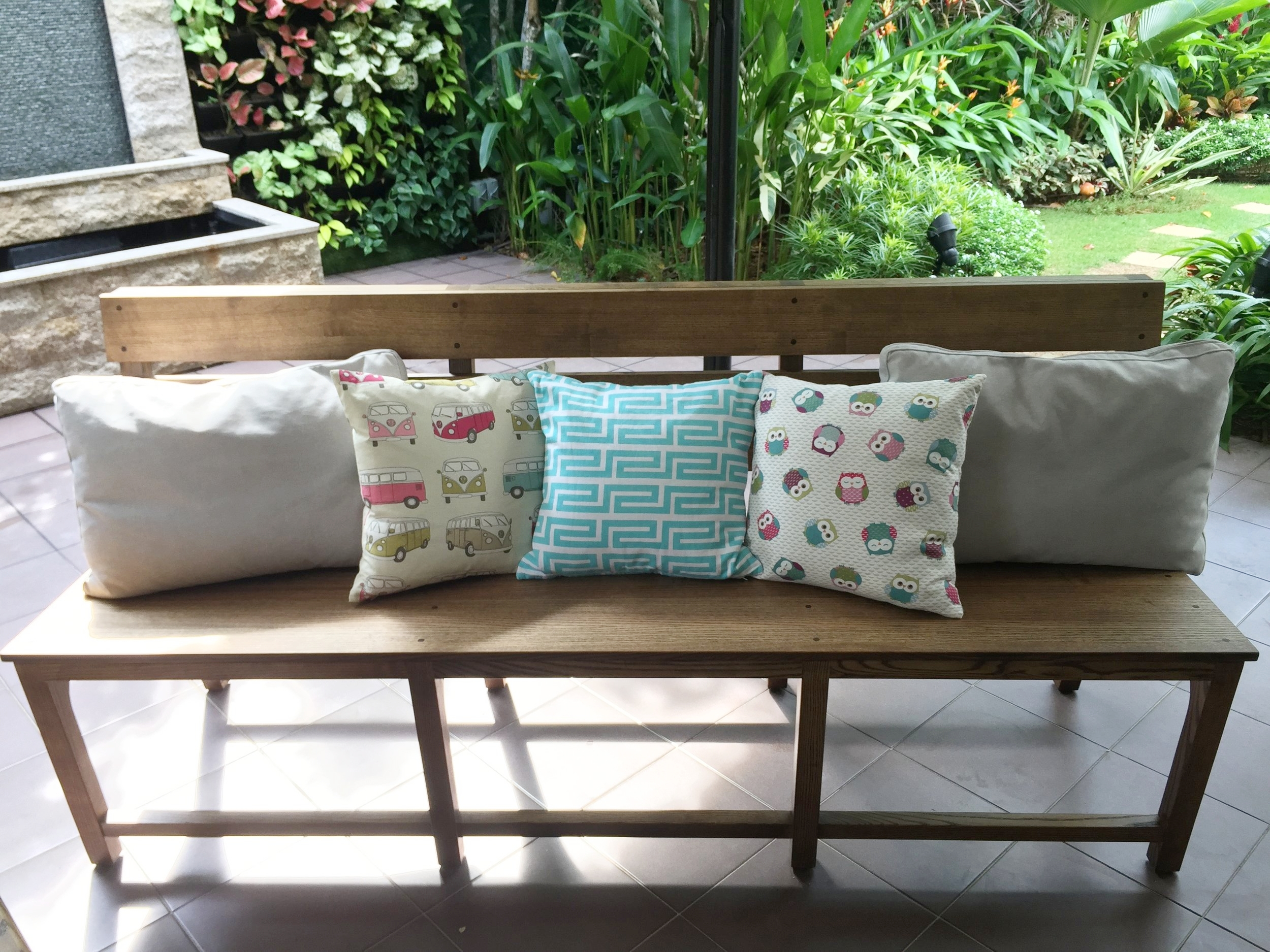 Spice up solid wood benches with colourful cushions and throws.