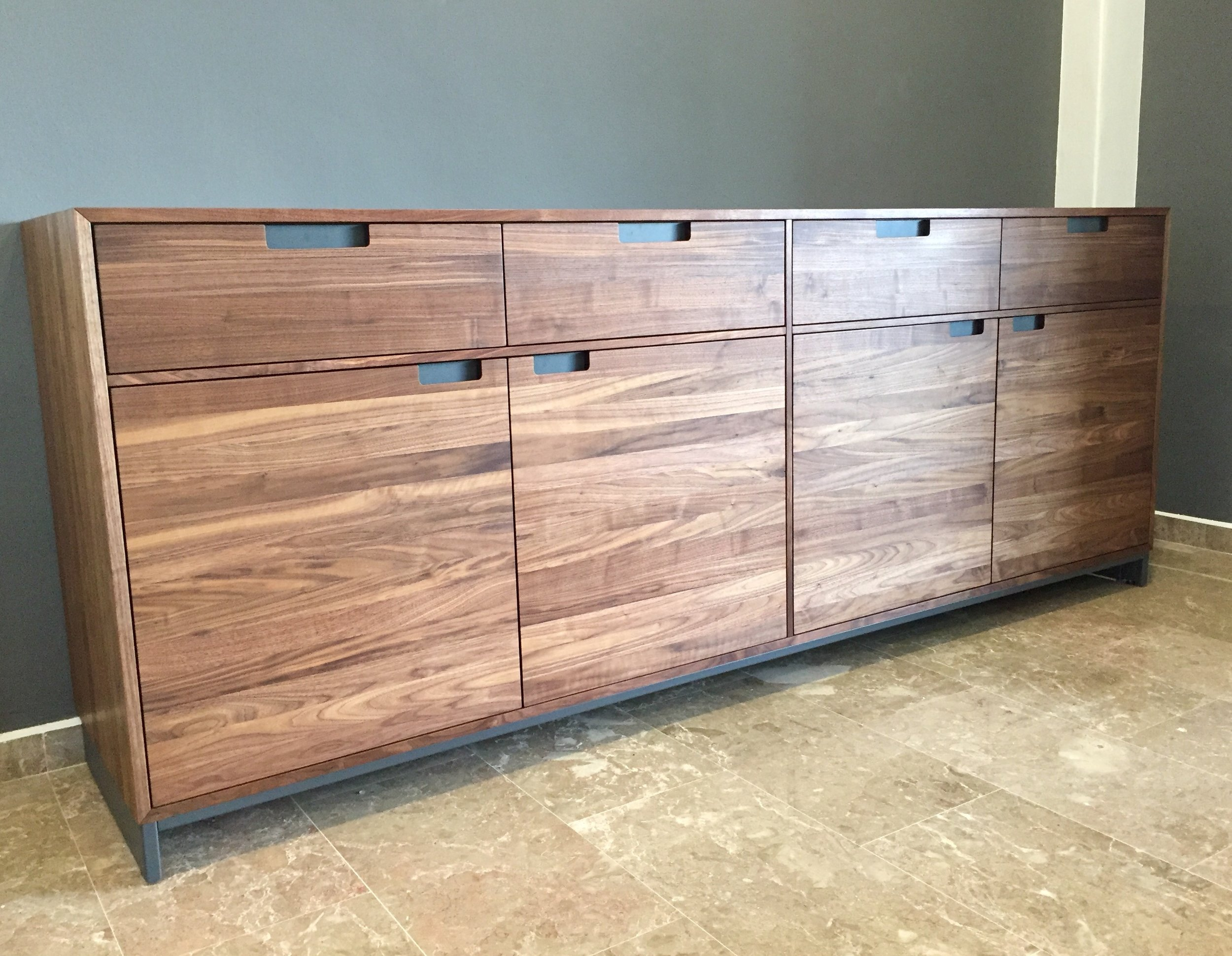 Standing handsome at the entrance of a 1700 sq ft apartment is a 2.35m long, 0.5m deep, with a 0.9m tall piece of solid Walnut Sideboard on powder coated steel legs.