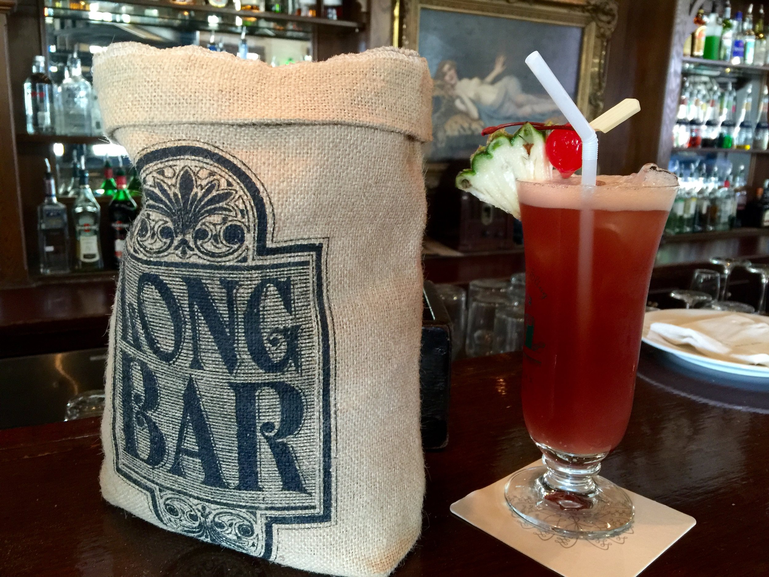 """The Long Bar at One Raffles Place   If you've ever heard of a """"Singapore Sling"""" - this bar is the reason why. Step in for a bit of history, and leave with a smile on your face. With a slightly tropical flair, great atmosphere, and a storied history dating back to Singapore's earliest days,the long bar is worth a visit even if you don't drink."""