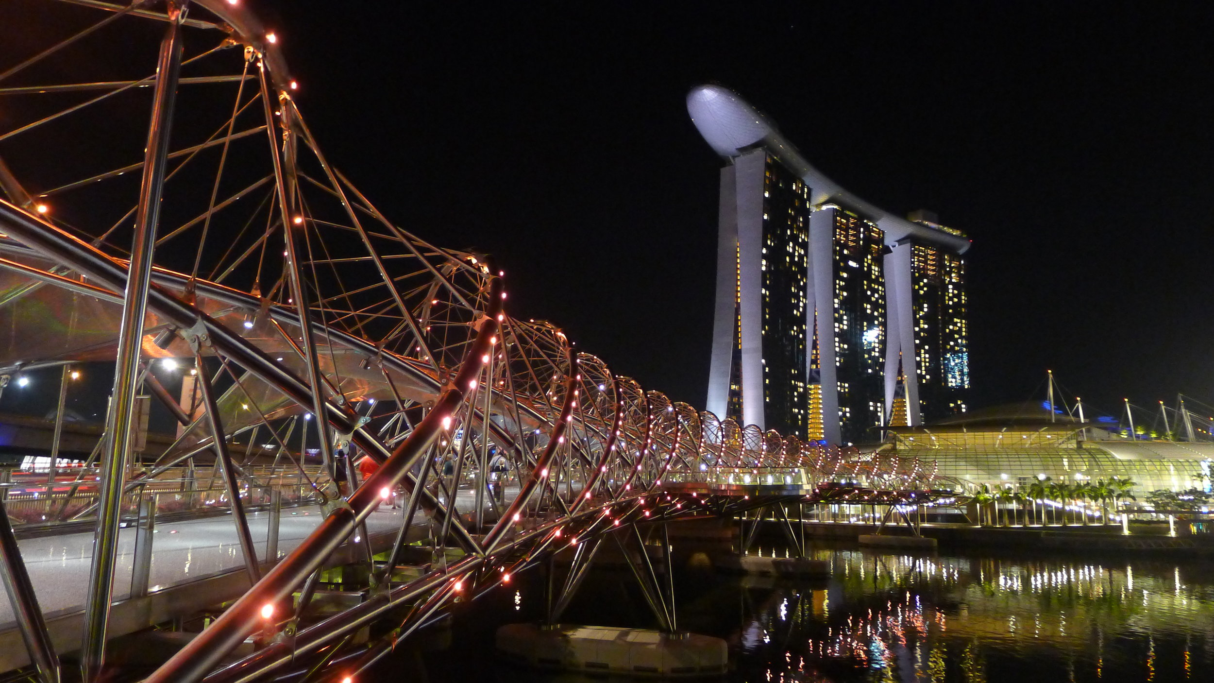 """HELIX BRIDGE   Located between the Marina Mandarin and the Marina Bay Sands is one of the coolest bridges that I have ever seen. Entrances can be found near the Youth Olympic Park and (conveniently) the ArtScience museum, this bridge is modeled after the double-helix structure of a DNA molecule and really encapsulates the modern design that Singapore epitomizes.  Credit: """" Marina Bay Sands - Singapore """"Photo by  Bro. Jeffrey Pioquinto, SJ"""