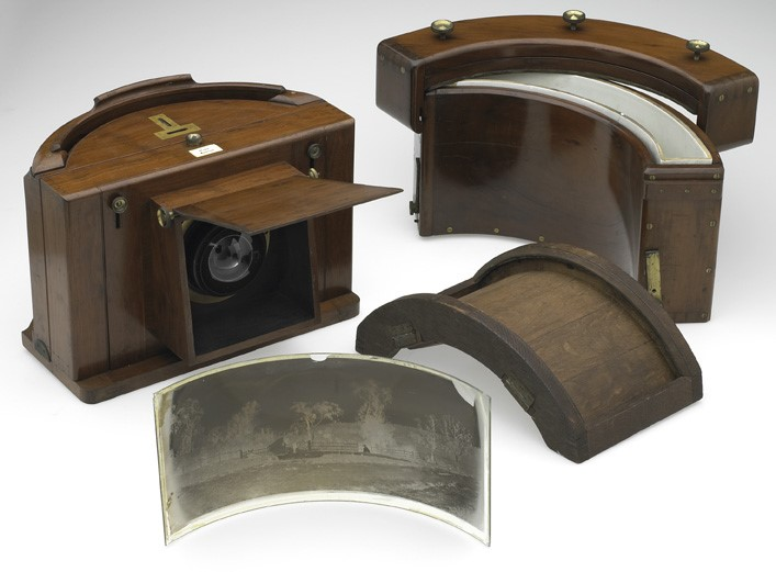 Panoramic camera, designed in England by Thomas Sutton   c1861  , and one of about 30 produced. The camera lens is made up of two hollow glass hemispheres. The flap on the front of the camera lifts up to allow an image to be taken.        Credits:  Reproduced courtesy of Museum Victoria        Creator:  Thomas Sutton, designer, c1861                      Jon Augier, photographer   Identifiers:  Museum Victoria image number MN 14973                      Museum Victoria object registration number ST 029632                      TLF resource R6388          Source:  Museum Victoria,    http://www.museum.vic.gov.au/