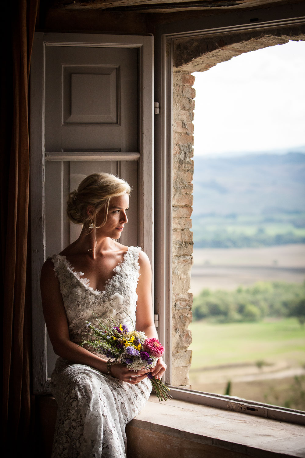 Wedding photo of a bride in a window in Tuscany