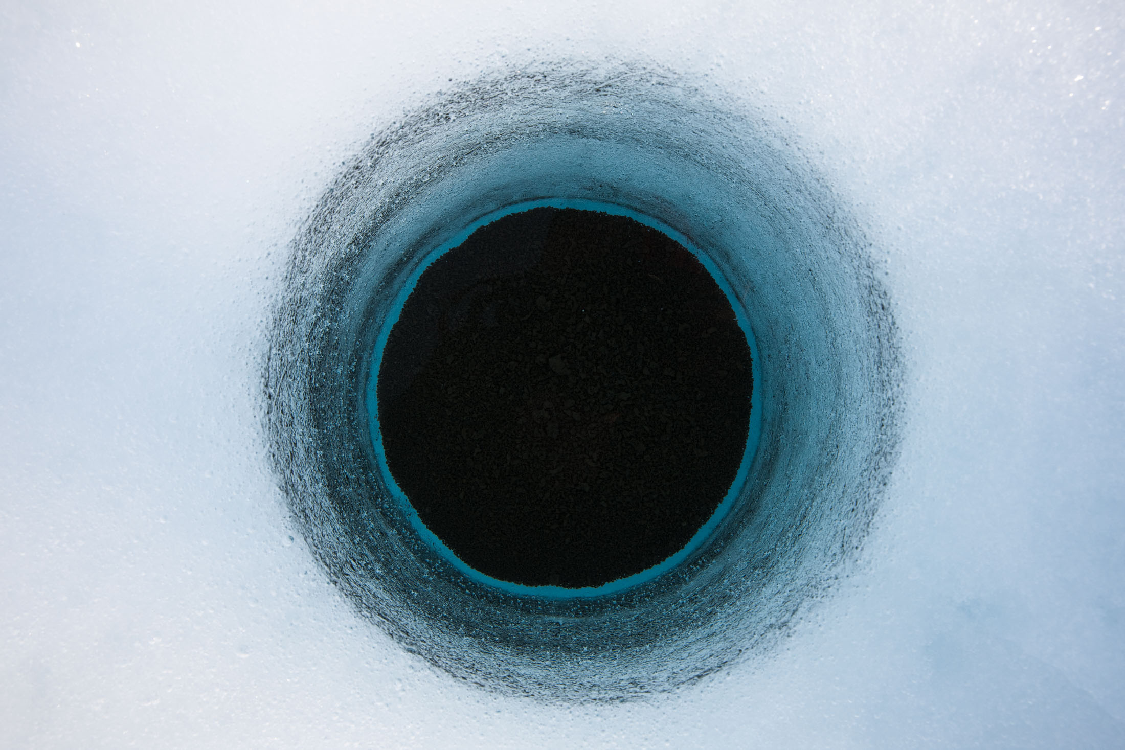 A hole made of cryoconite on the surface of the Greenland ice sheet