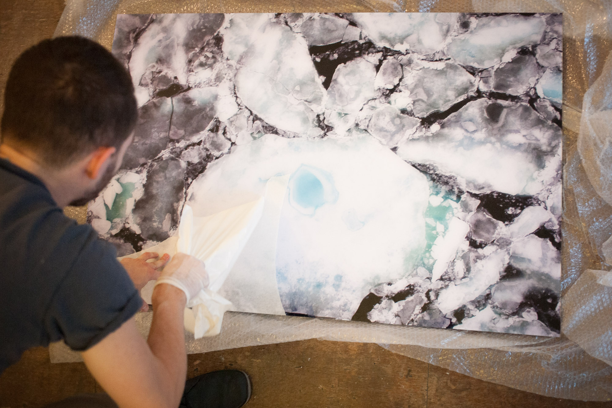 A photograph of sea ice is unwrapped prior to hanging in a gallery