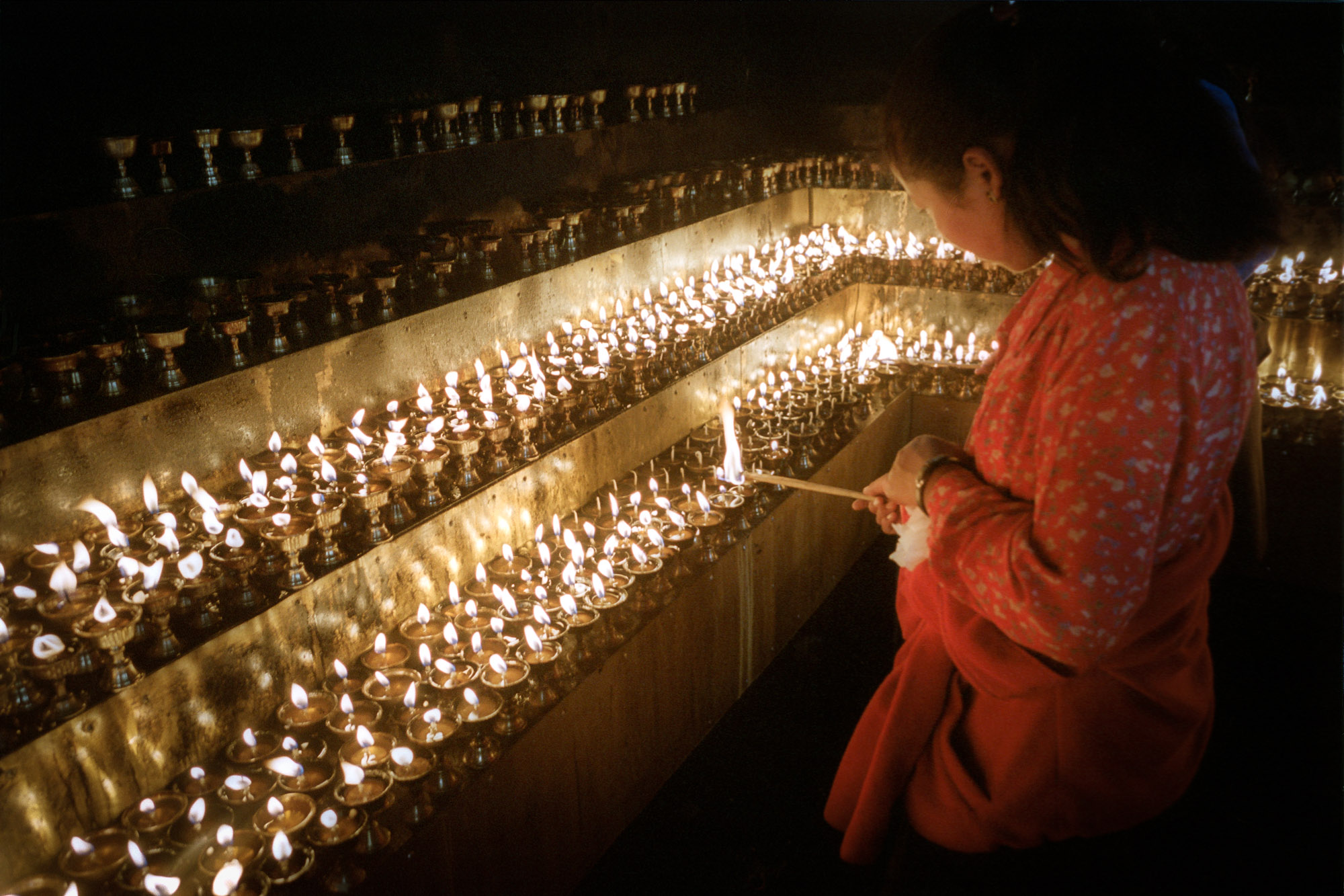 Lighting butter lamps outside the Jokhang Temple