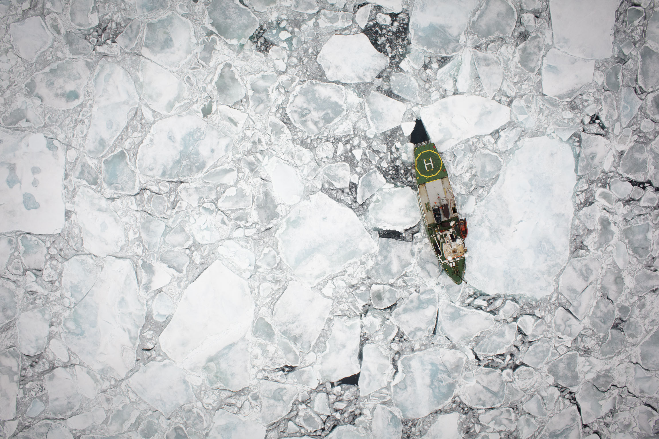 A tiny ship photographed from the air in Arctic sea ice