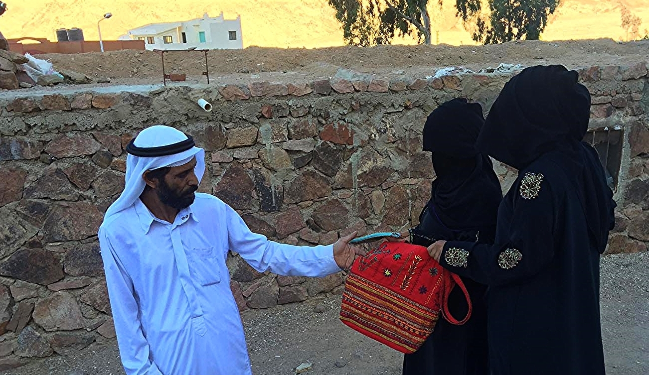 Mohamed receiving Bedouin crafts from the women
