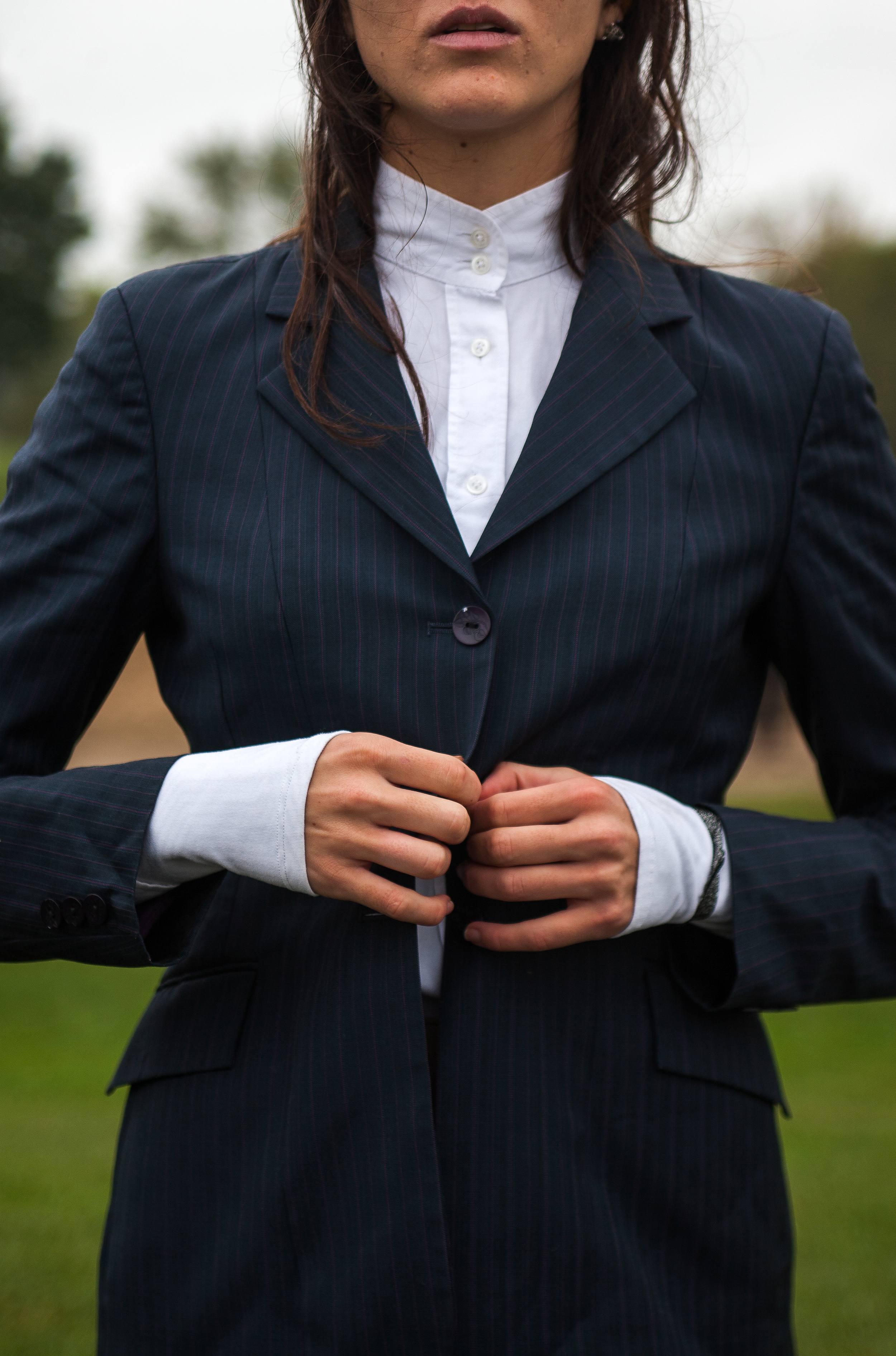 "Alyse Solomon, a junior and intermediate Hunt Seat rider for the Central Michigan University Equestrian club team, buttons up her show jacket as she gets dressed for her first show of the season at Woodbine Farms in Chelsea, Mich. on Sunday, Oct. 4, 2015. Hunt Seat is a style of forward seat riding. ""You use your core muscles as well as leg muscles no other sport targets,"" said Solomon."