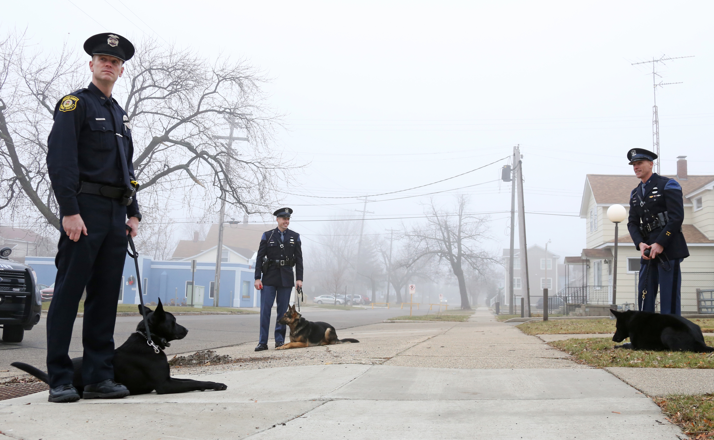 Law enforcement officers stand next to their police dogs keeping them calm and away from one another before the start of a ceremony commemorating the 20th anniversary of the shooting death of the Grand Haven police officer Scott Flahive in front of the Grand Haven Eagles building downtown Grand Haven on Dec. 13, 2014.