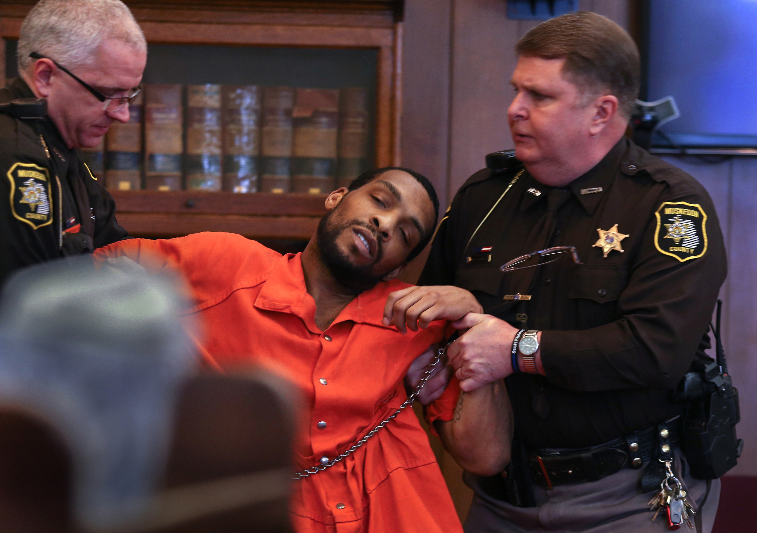 Robert Gee collapses in court Thursday, Feb. 26, 2015, after learning of his convictions before Judge Timothy G. Hicks during his bench trial in Muskegon County's 14th Circuit Court. Gee is charged with first-degree premeditated murder in the shooting death of 26-year-old motorcyclist, Jacob Rameau, last June in Muskegon Heights, Mich.