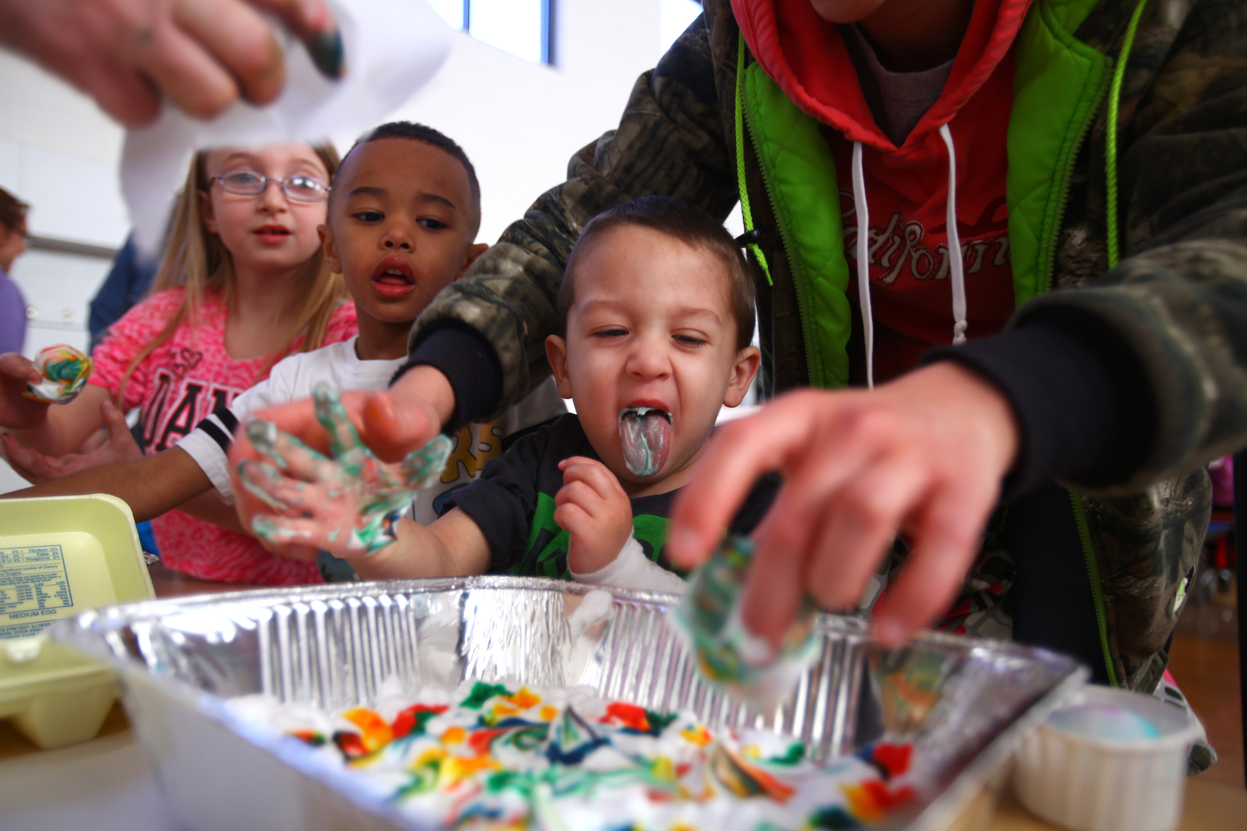 Emerick Hobby, 2, sticks out his tongue after eating a handful of food coloring and shaving cream while dying an Easter Egg with the help of his mother at Orchard View Early Elementary Saturday, March 28, 2015. Emerick's brother Bentlee Hobby, 4, and friend Skylar Wright, 9, look over his shoulder to see what he has done.