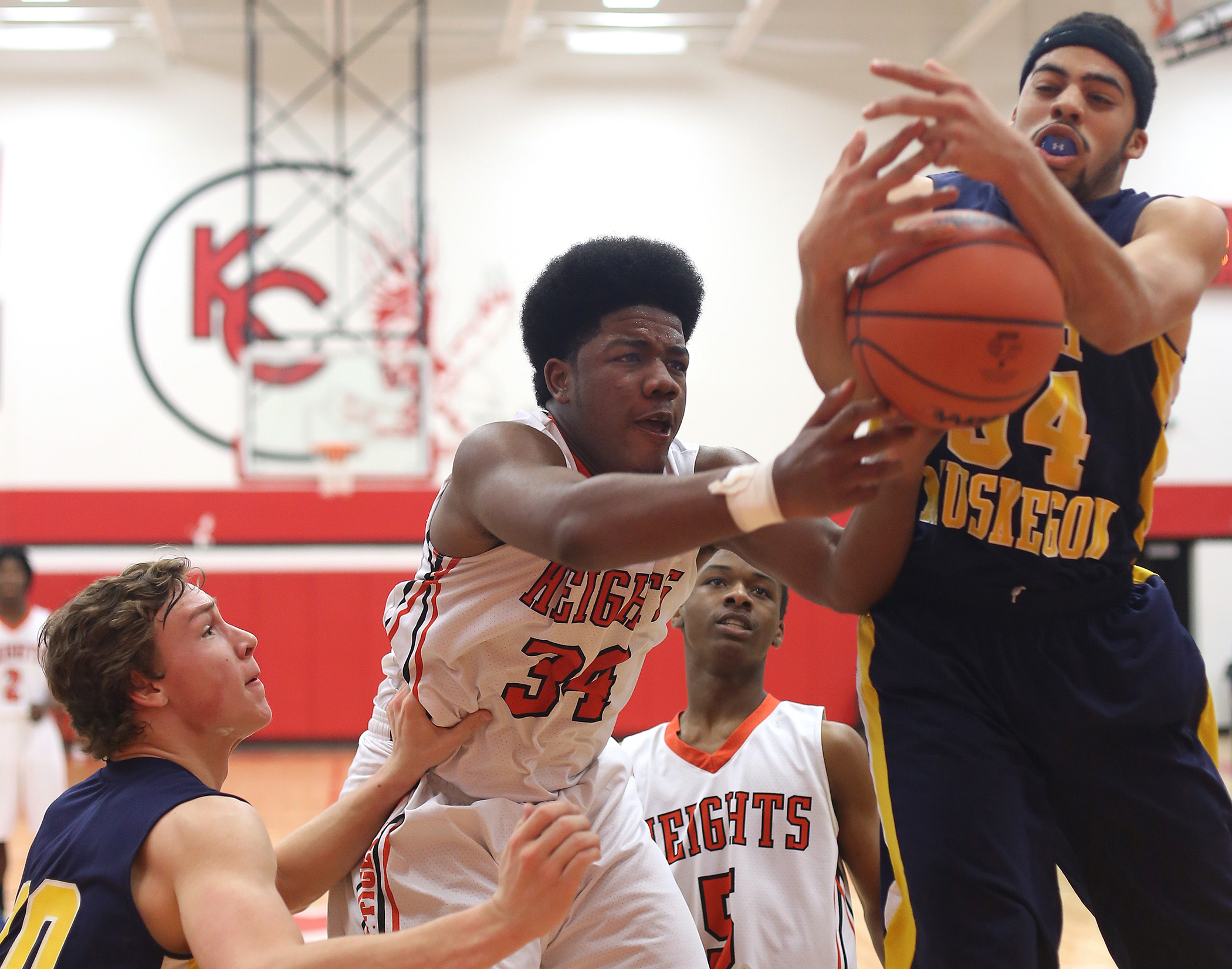 Keishon Watson (34) of Muskegon Heights Academy and Vernonell Smith of North Muskegon, right, fight for the rebound in the second quarter of their game at Kent City High School Friday, March 13, 2015. North Muskegon outscored the Tigers in a back-and-forth game to pull out the win and break the 12-year district drought.