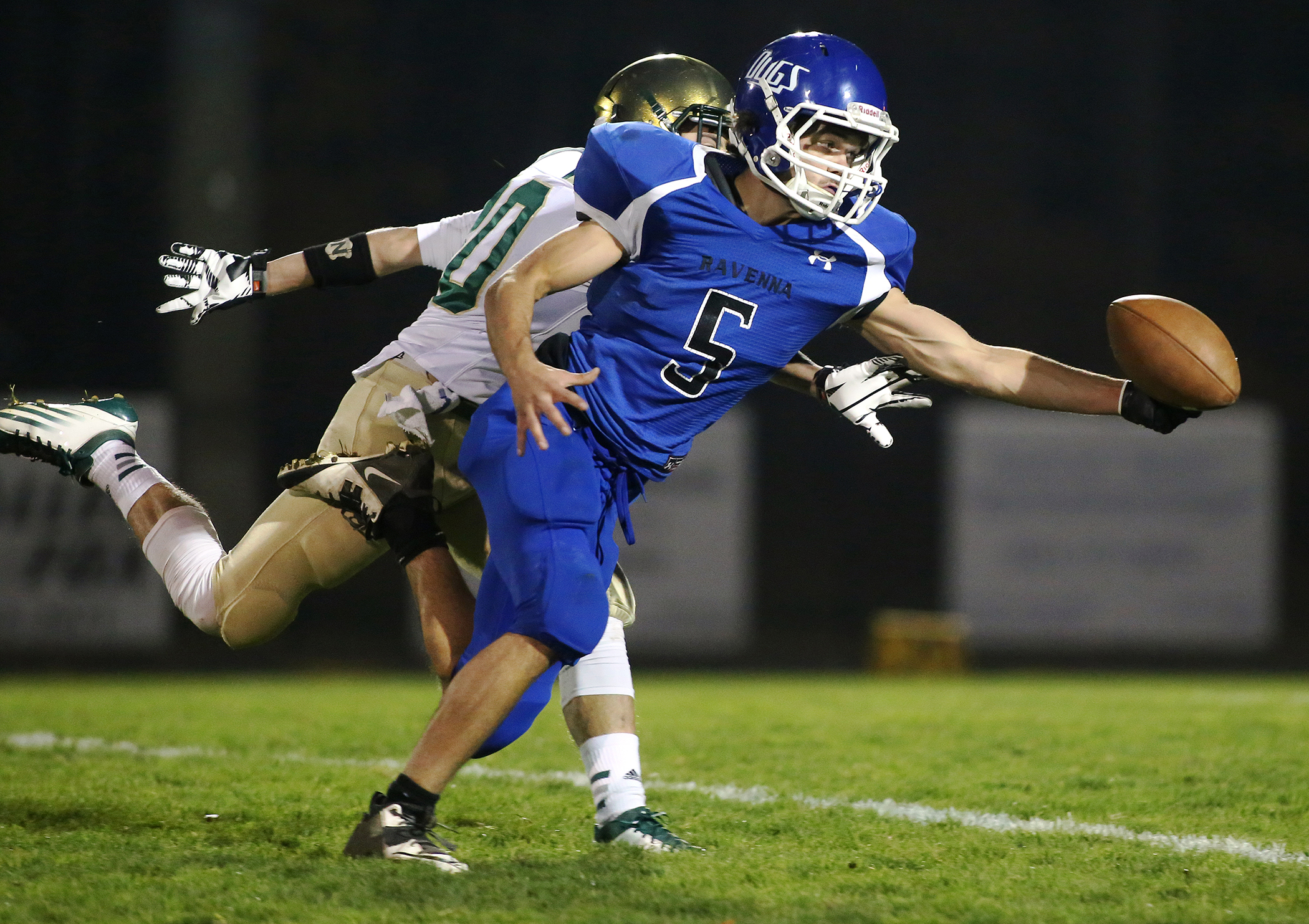Dakota Hudson (5) of Ravenna attempts to complete a catch on a fourth down while defended by Anthony Woodard of Muskegon Catholic Central in the first quarter of their game in Ravenna on Oct. 24, 2014. The play was not completed and turned over to MCC. Muskegon Catholic Central won 45-0.
