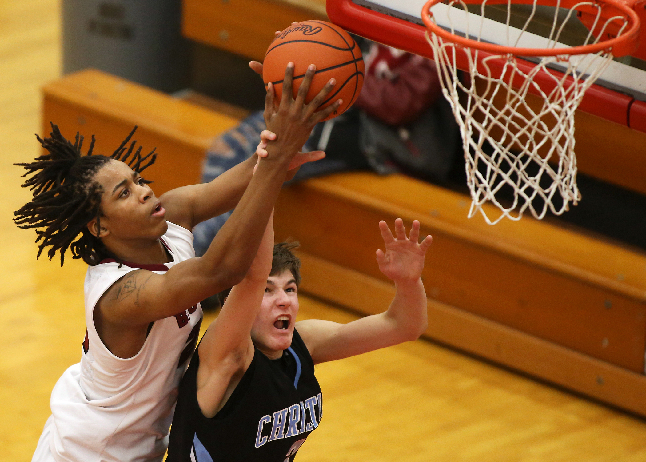 Deyonta Davis of Muskegon goes up to catch a pass against defender Emmett Warners of Christian in the third quarter of their game at Muskegon High School Tuesday, Jan. 20, 2015. Muskegon won 65-54.