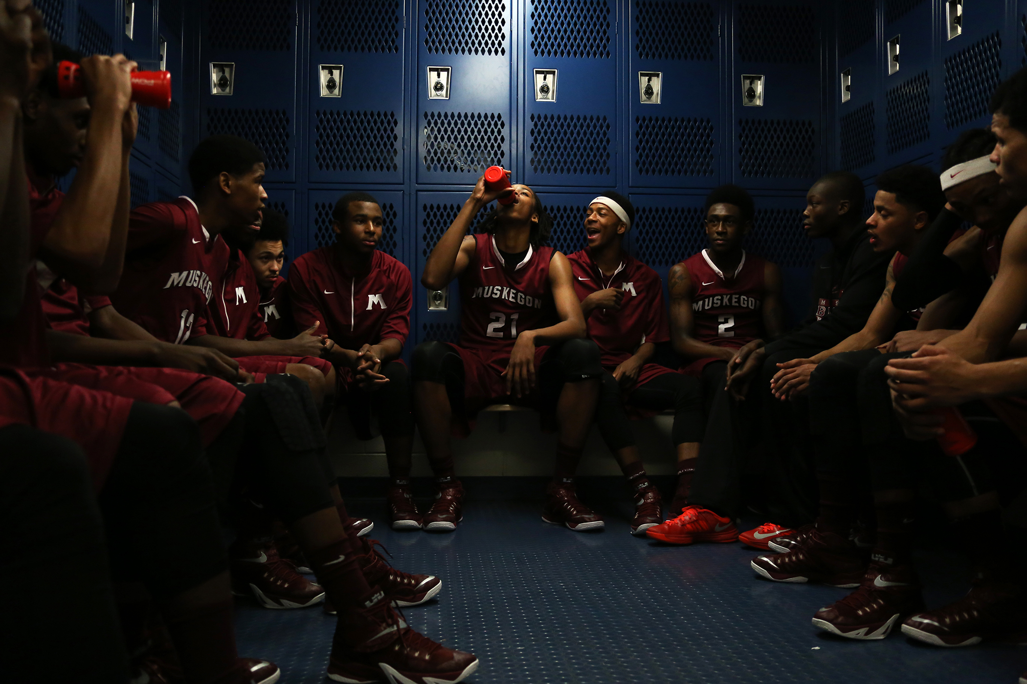 Deyonta Davis of Muskegon, center, hydrates himself surrounded by his team during halftime in the locker rooms at Mona Shores High School Friday, Jan. 16, 2015.