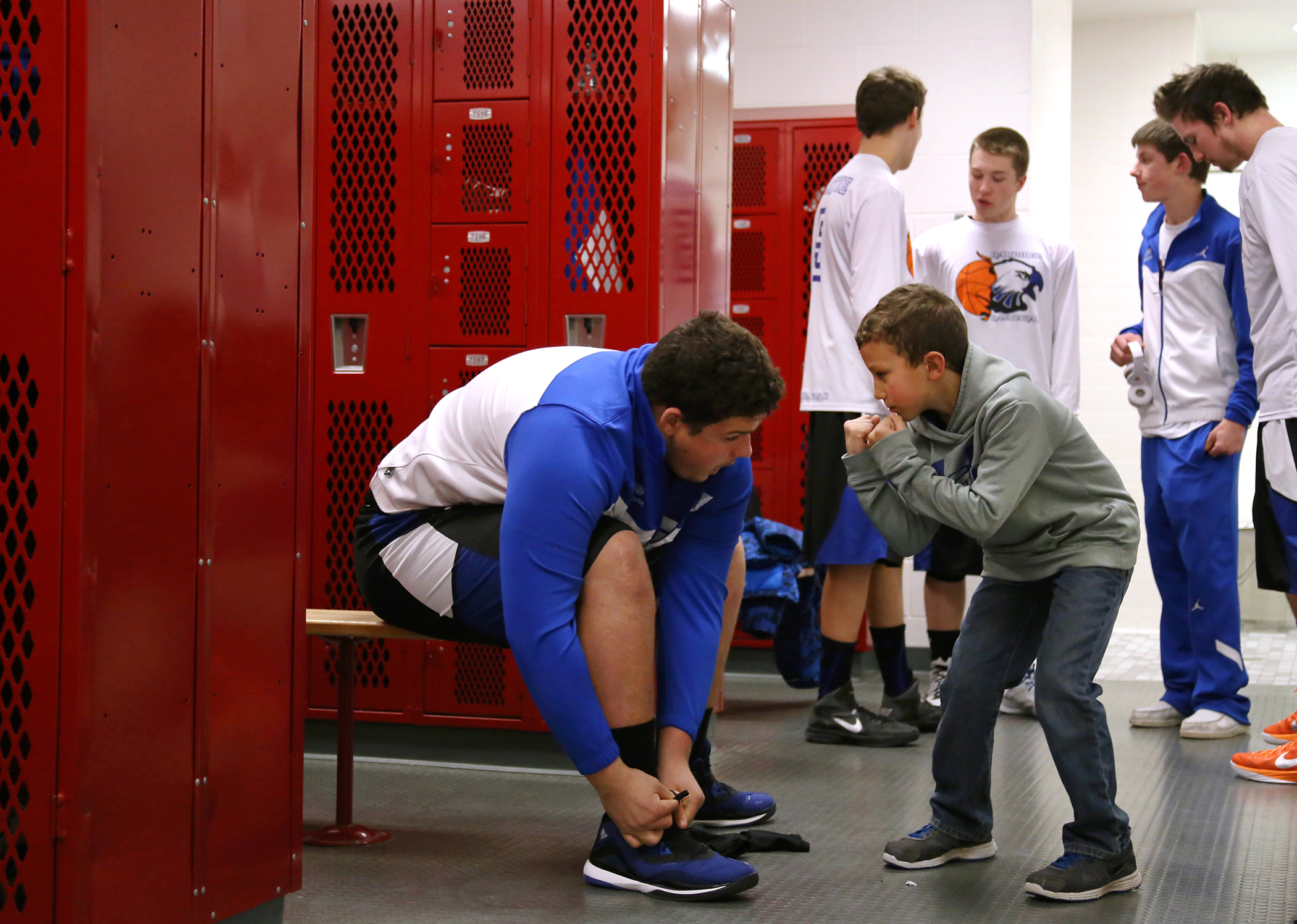 Peyton Ruel, 8, attempts to pump up Tony Curry of Oakridge as he ties his shoes in the locker room before their game against Spring Lake at Spring Lake High School Tuesday, Jan. 13, 2015. Spring Lake won 59-41.