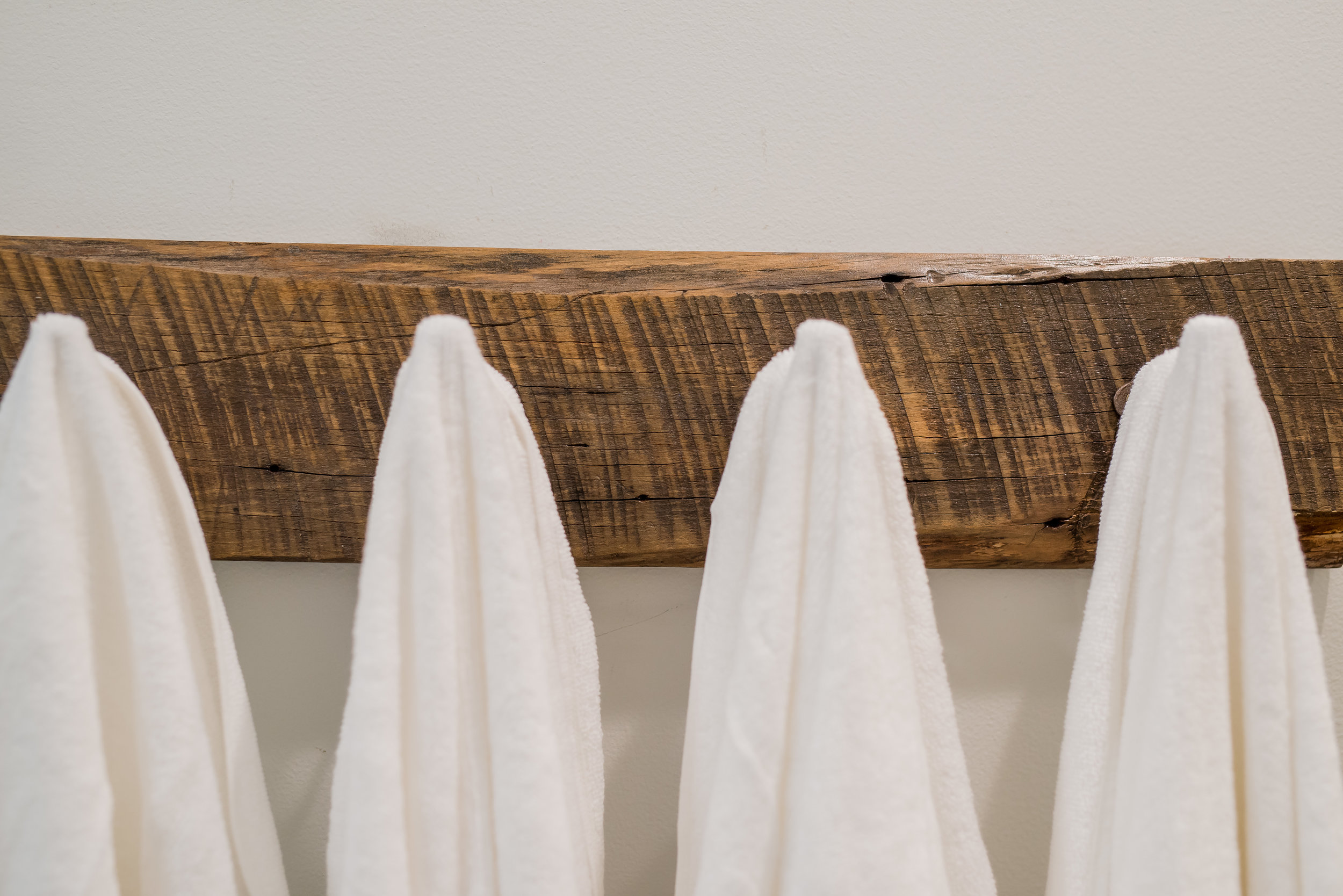 We made our own towel rack from a piece of barn wood given to us by dear friends! I love the pattern of the sawmill blade that came through! It's perfect.