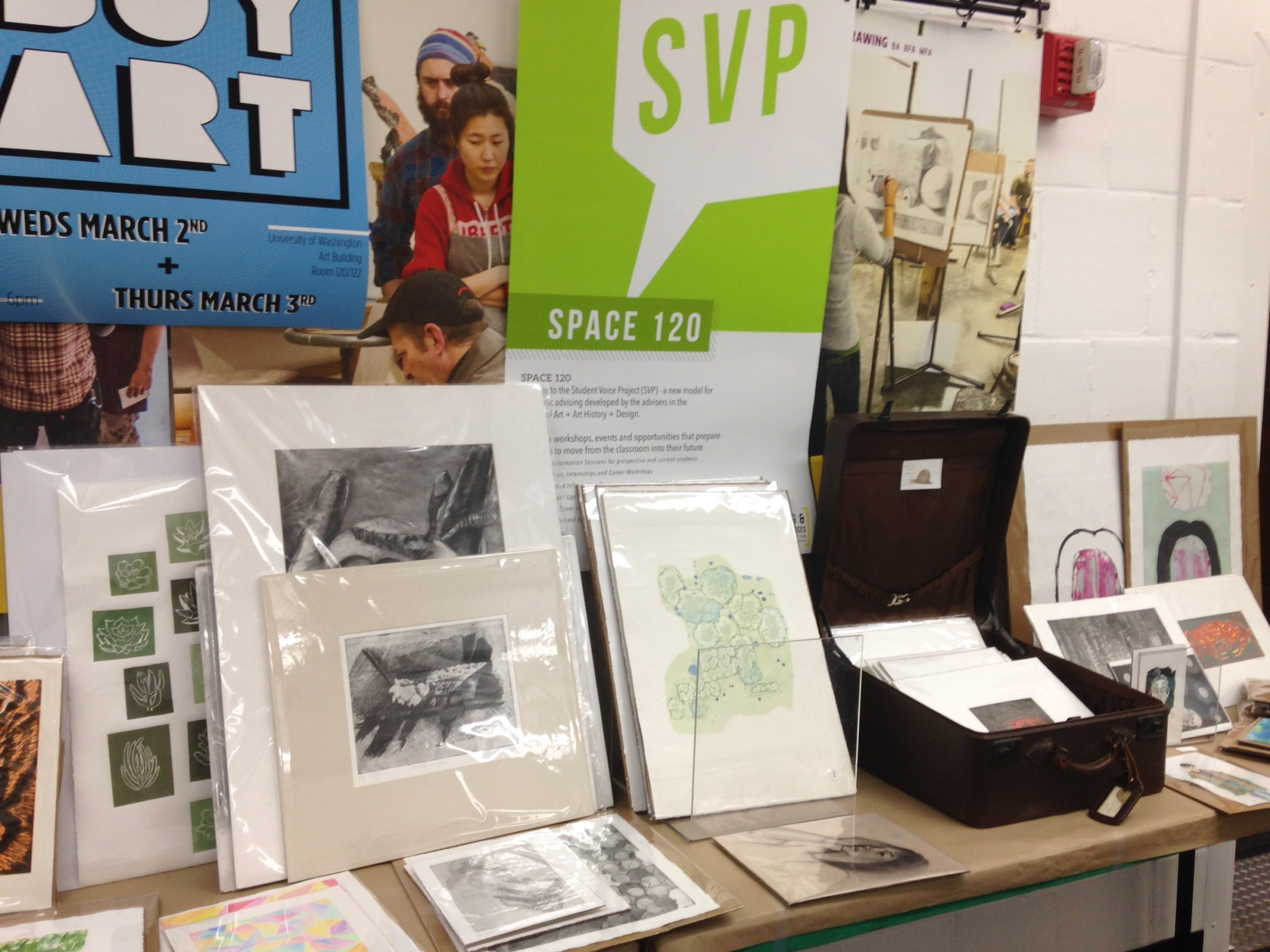 Tables overflowing with art at the BUY ART event. Up front you can see an etching print of mine (in mat) with a charcoal drawing of mine right behind it .