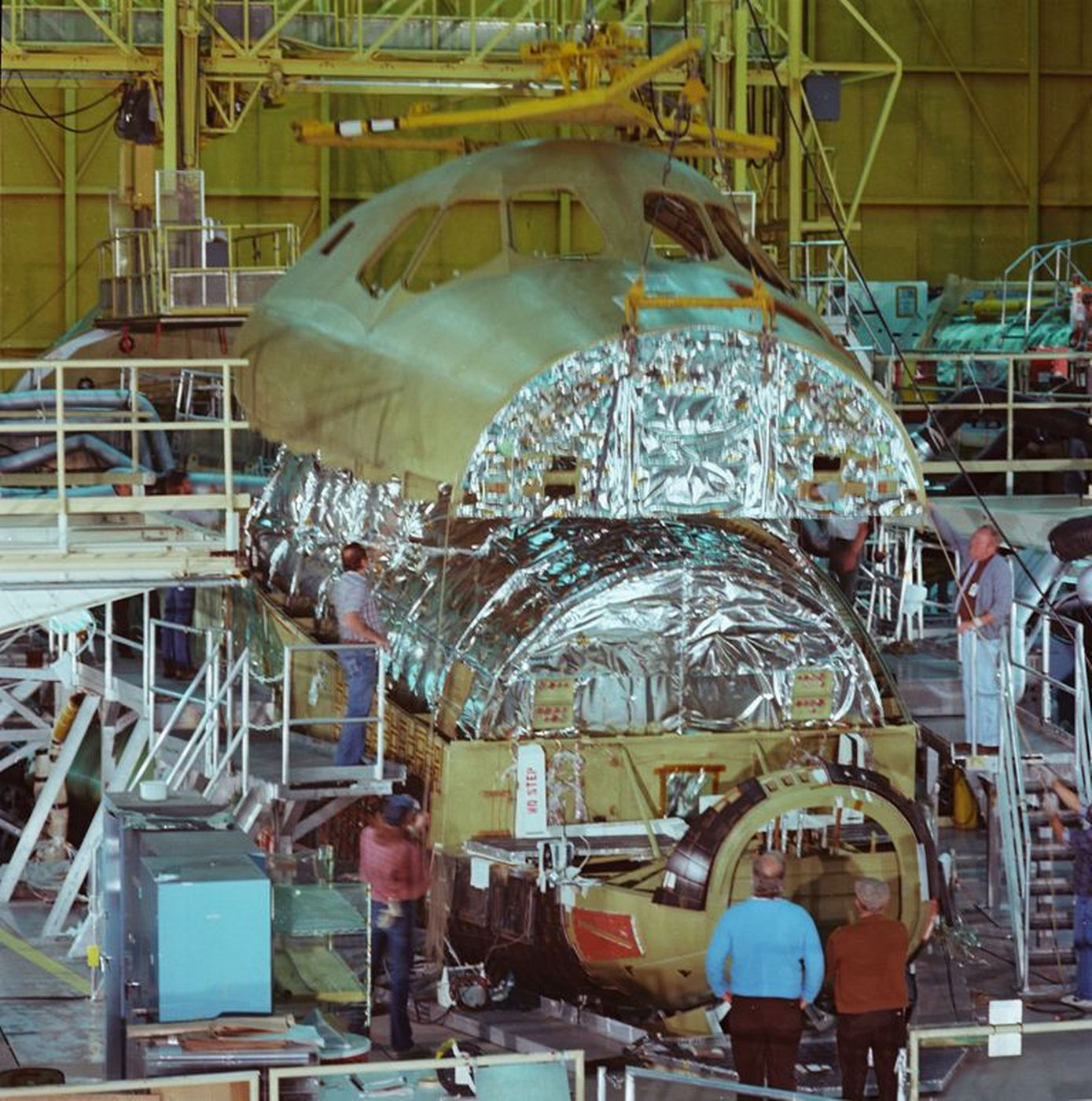 The upper fuselage is being installed onto Atlantis' lower fuselage, with the crew module already secured. This photo was taken at Rockwell's Palmdale facility on April 25, 1984.jpg