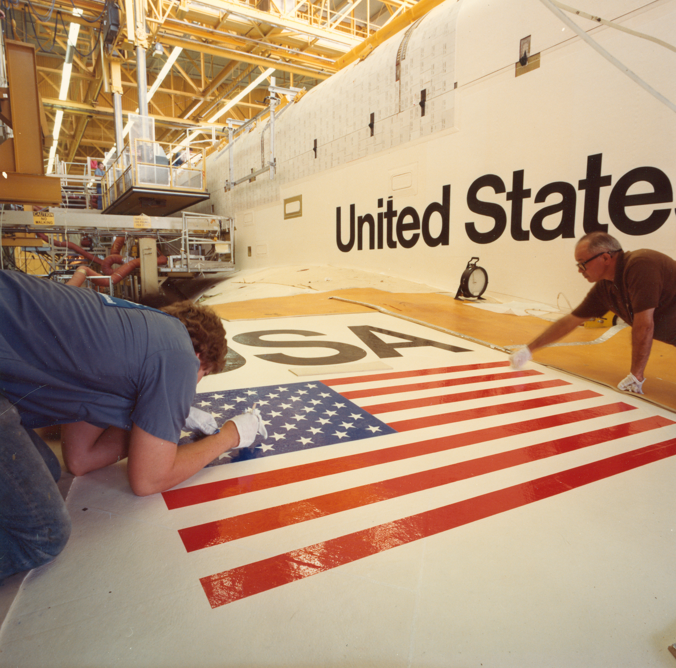 workers finish lettering and decals on shuttle at rockwell.jpg