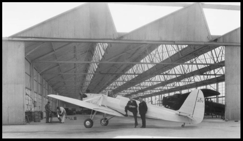 """Above- Bert Kinner left with foot on wing of Security """"Airster"""" in Building 1 of Downey plant at 12214 Lakewood Blvd.  Image- Dick Whittington Studios."""