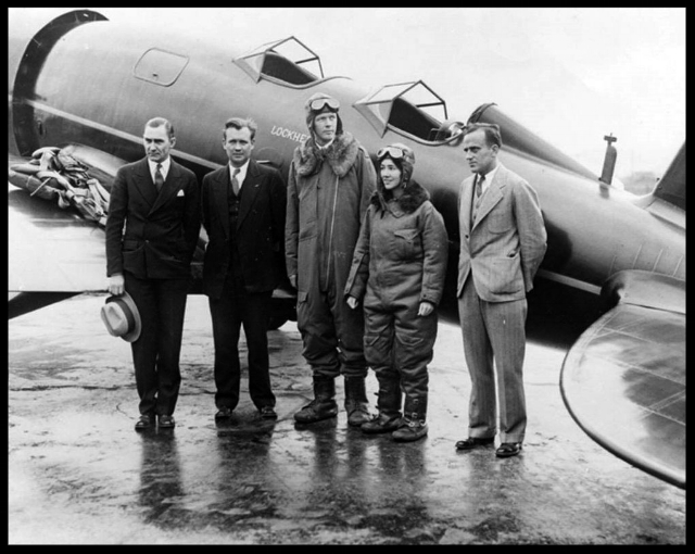 Above- 1930, view of Charles A. Lindbergh and his co-pilot/navigator, Anne Lindbergh beside their  Sirius , built according to the specifications of Lindbergh, by  Lockheed . Jerry Vultee is on the far right.