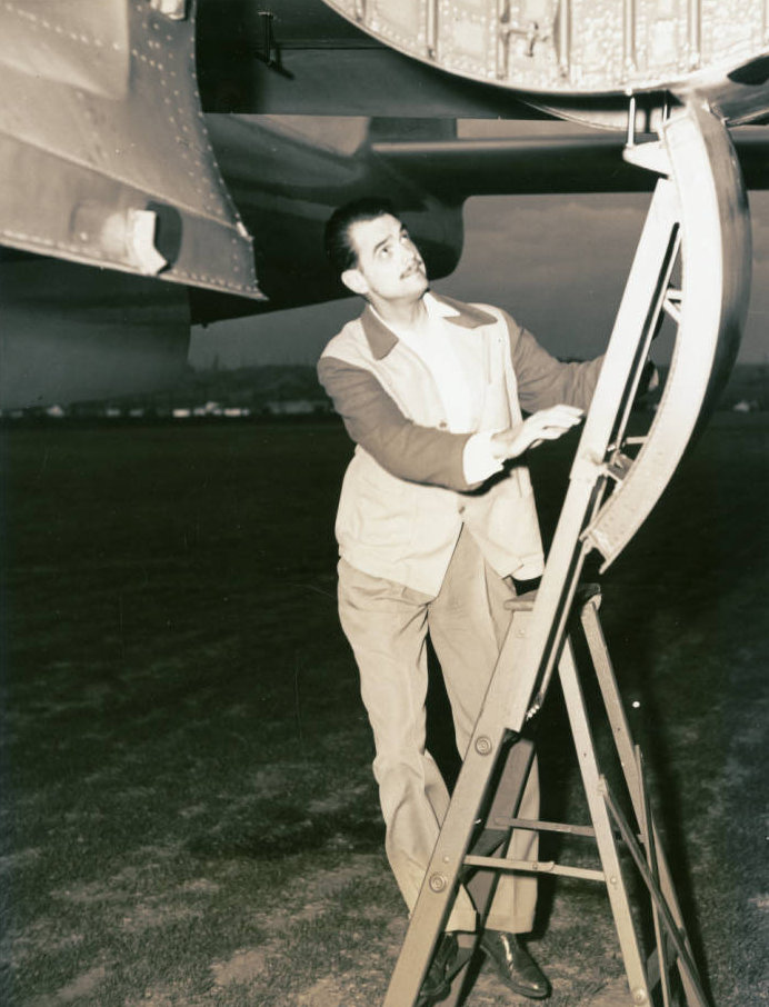 Photograph of Howard Hughes on ladder under the XF-11, April 3, 1947