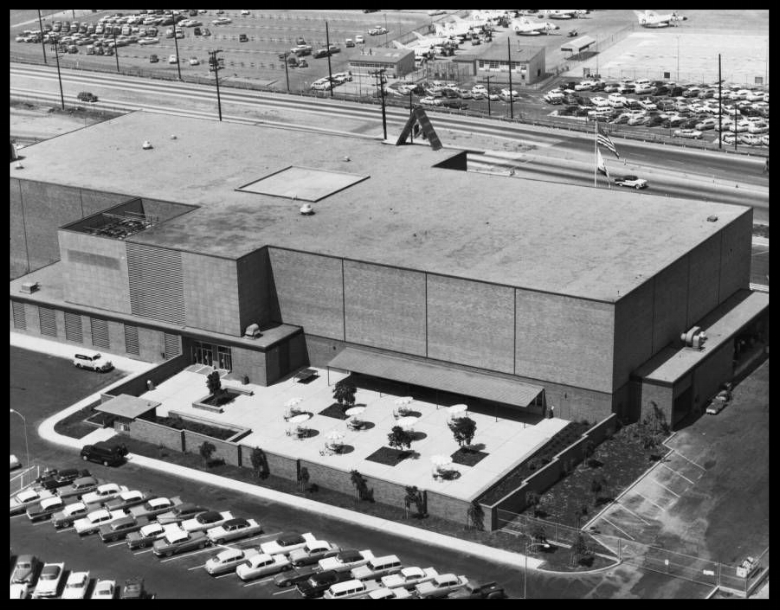 North American Aviation headquarters in Inglewood/ El Segundo c1960. Automobiles can be seen in a crowded parking lot int he foreground at left, and another parking lot is visible across the street in the background. In the background at right, Douglas Skyray fighter planes can be seen lined up at an airport. Photo from North American Aviation Inc. public relations library.  Image- USC Digital.