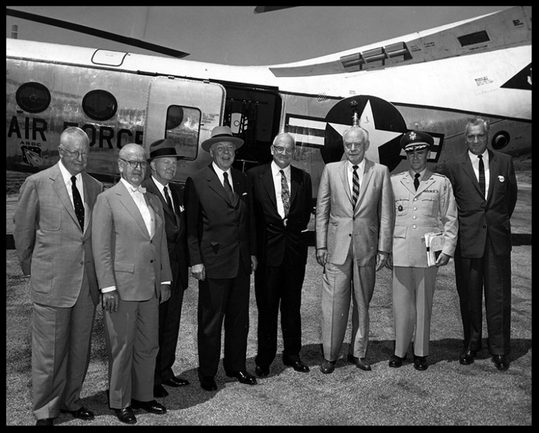 """Shown above are Secretary of Army Wilbur M. Brucker and members of his party as they arrived at North American's Propulsion Field Laboratory in Chatsworth to watch engine test stand firing. From left are, Courtney Johnson, deputy assistant secretary for logistics; Dr. William Martin, director research and development; Secretary Brucker; Don Belding, president of Airport Commissioners; J. H. Kindelberger, chairman of board for North American aviation; Lt. Col. T. R. Cook, secretary's aide, and A. T. Burton, a North American vice president."""" August, 1957.  Image- LAPL"""