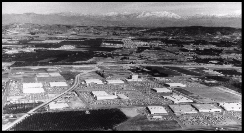 Aerial view of Autonetics Division of North American Aviation Inc., (later Rockwell International and then Boeing North American), located at 3370 Miraloma Avenue, Anaheim, was established in 1957; image shows Autonetics buildings and parking lots on Miraloma Avenue (horizontal, center); Carbon Canyon Diversion Channel runs diagonally down to left foreground; snow-covered Sierra Madre Mountains visible in background.