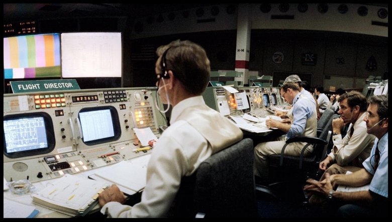 Flight director Charles R. Lewis (left) studies a chart display on his console's monitor in the mission operations control room (MOCR) in the Johnson Space Center's Mission Control Center, in April of 1981. Image- NASA