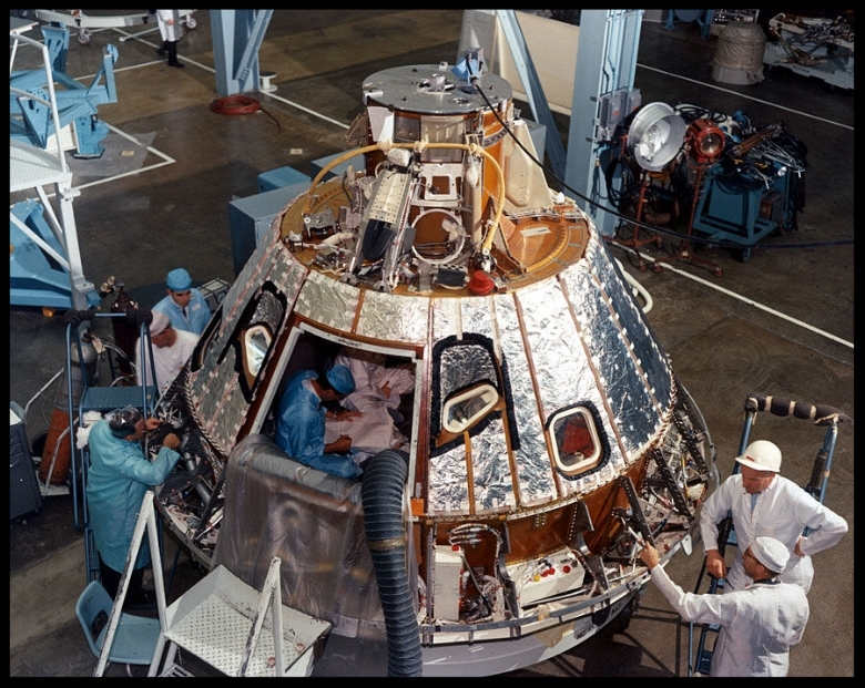 Command Module is shown at Downey during construction in April, 1966. North American technicians discuss their work.  Image- Boeing.