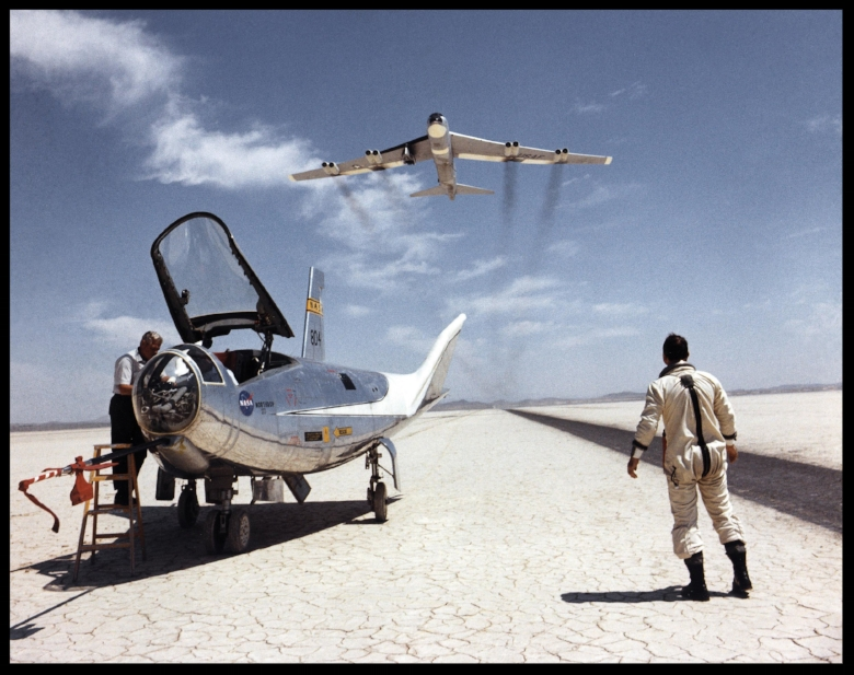 NASA research pilot Bill Dana takes a moment to watch NASA's NB-52B cruise overhead after a research flight in the HL-10. Image- NASA