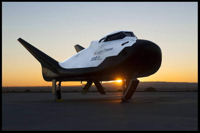 Above- Sierra Nevada Corp's Dream Chaser posed on ramp at sunrise at NASA Armstrong Flight Research Center in California where the aircraft has gone through a series of tests in preparation for flight. More...