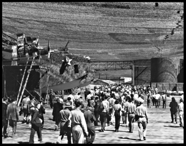 Above- Workers going home as shifts change, July 1943. Planes at left are PB2Y Coronado patrol bombers. Note camouflage netting overhead. Downey CA