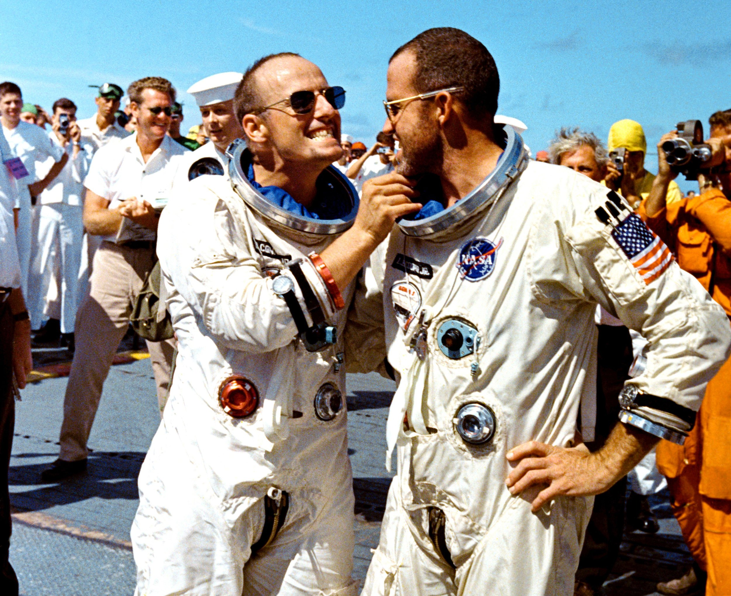 After recovery by the crew of the USS Lake Champlain on Aug. 29, 1965, Gemini V pilot Charles Pete Conrad tweaks the eight-day growth of beard of command pilot Gordon Cooper.