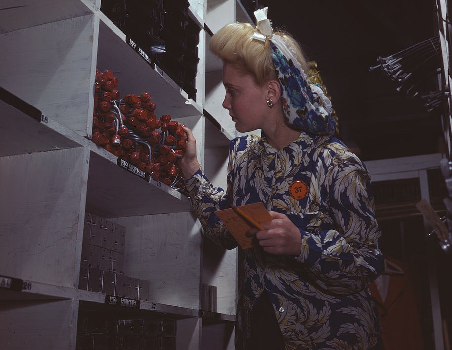 A clerk at the stock rooms of North American Aviation, Inc., checking to see if the proper numbers of parts were received and placed in the proper bin, Inglewood, Calif. 1942