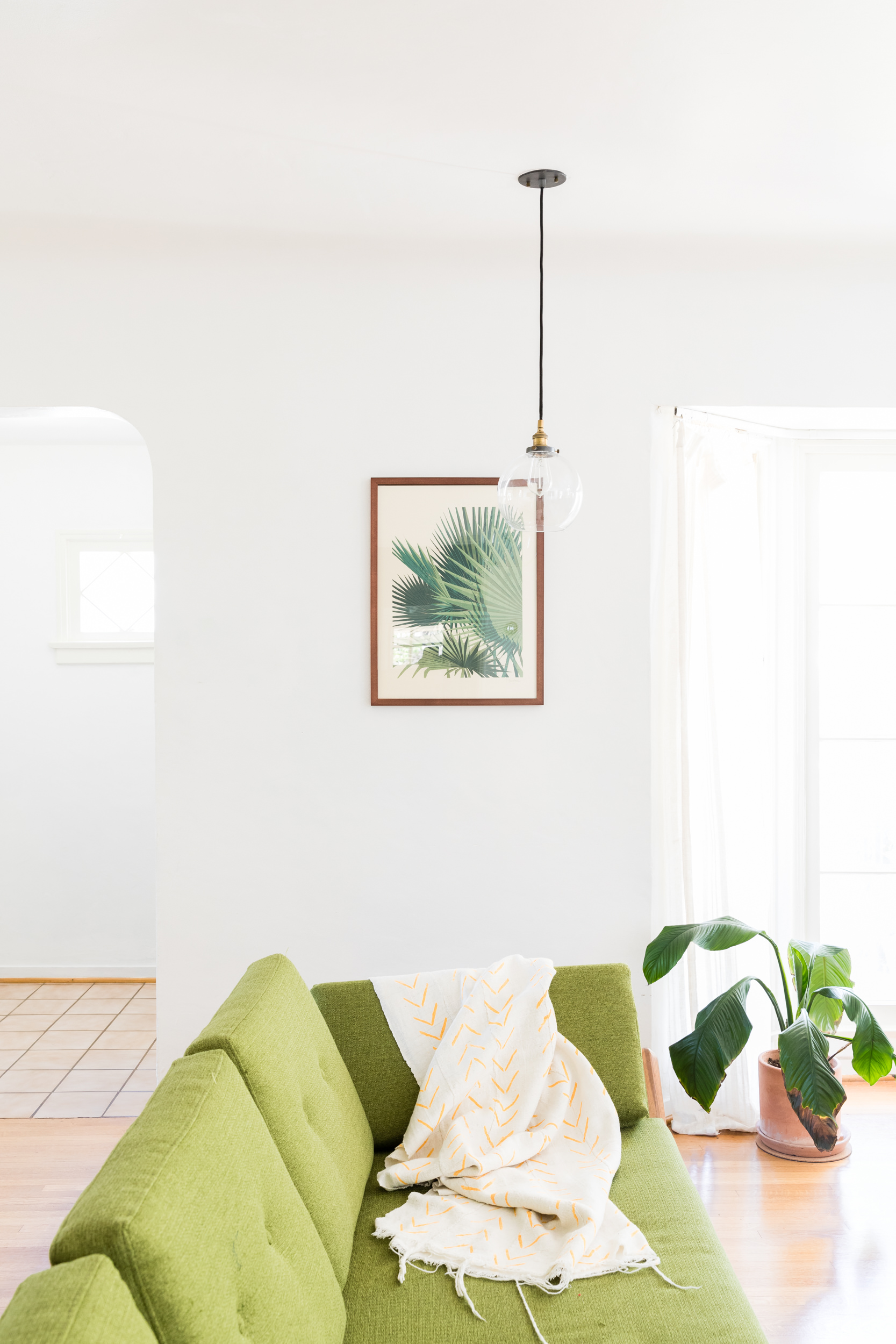 Los Angeles Airbnb mid mod living room with green couch, white walls, and glass pendant.