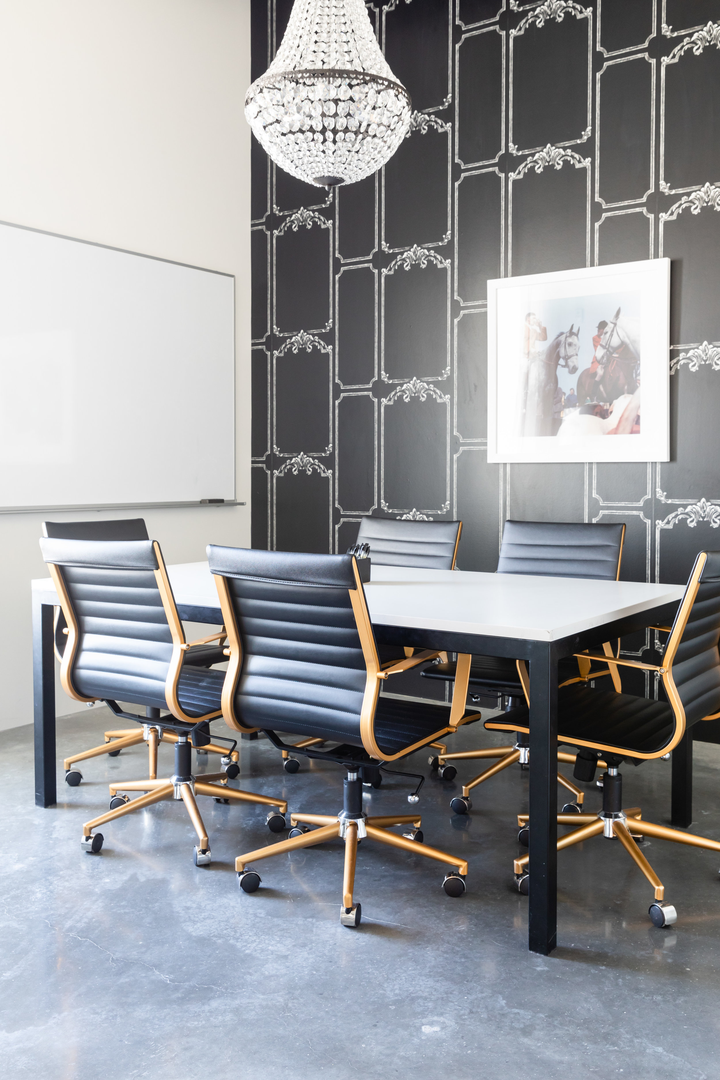 Black and white conference room with glass chandelier and black leather chairs.