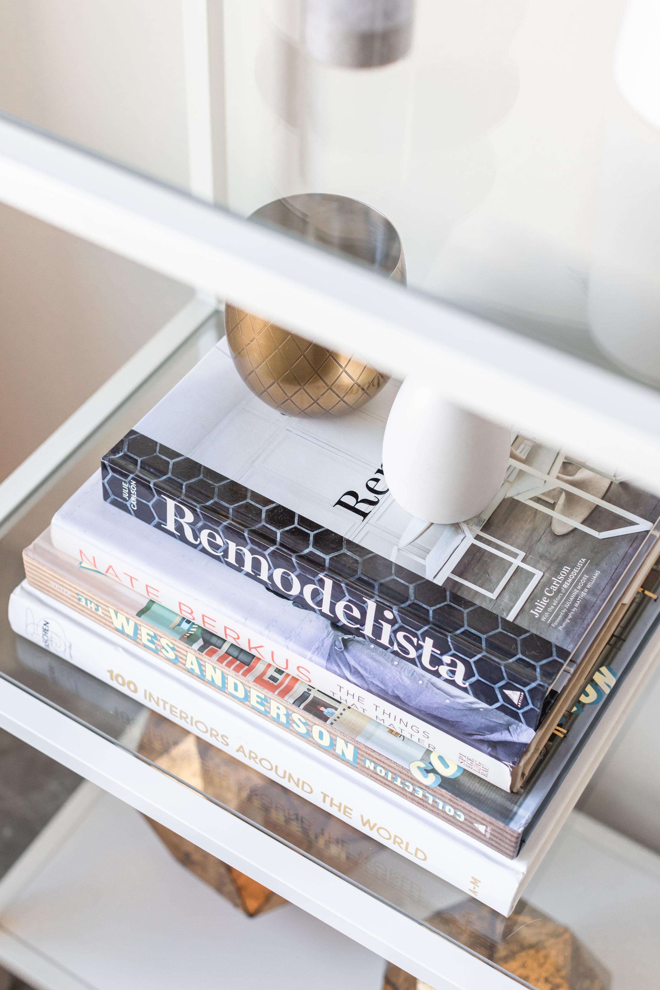 Stack of home decor books and brass and ceramic knick knacks on glass bookshelf.