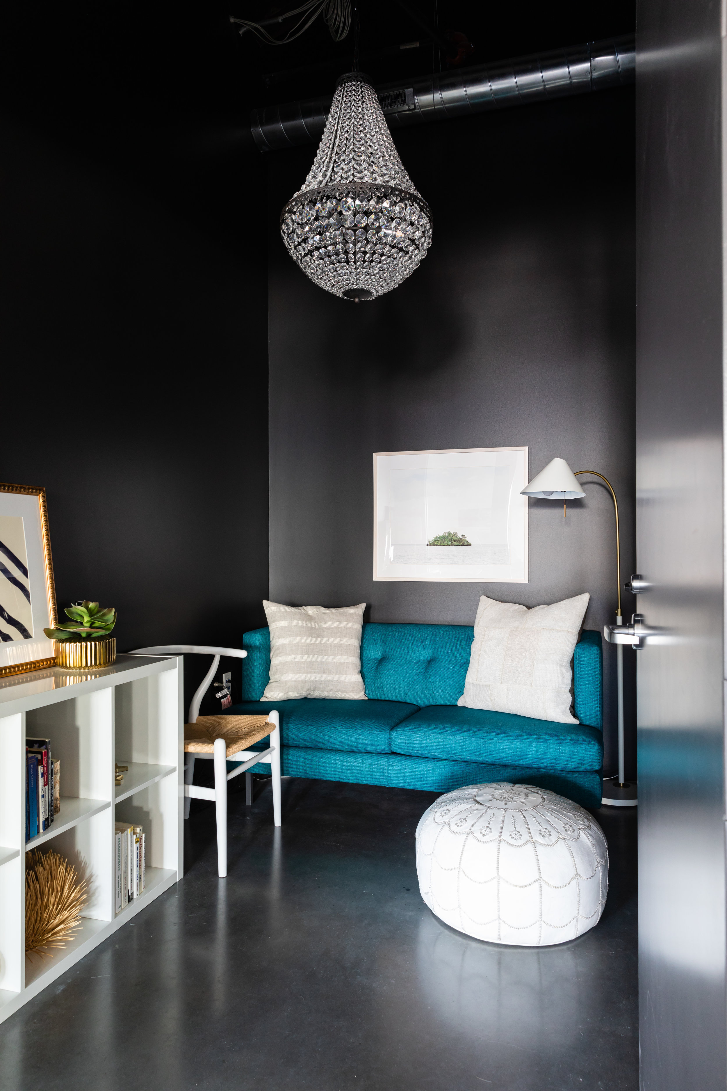 Conference room with black walls, white bookshelves, blue velvet couch, and glass chandelier.