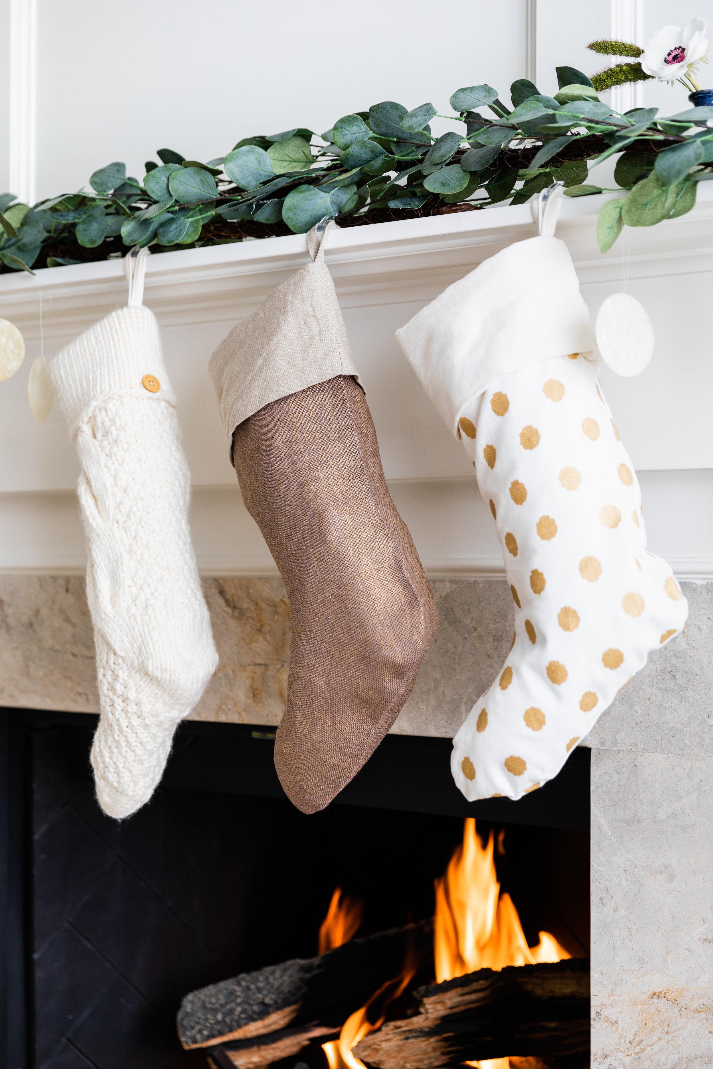 Pottery Barn Christmas stockings and garland hang on mantle.